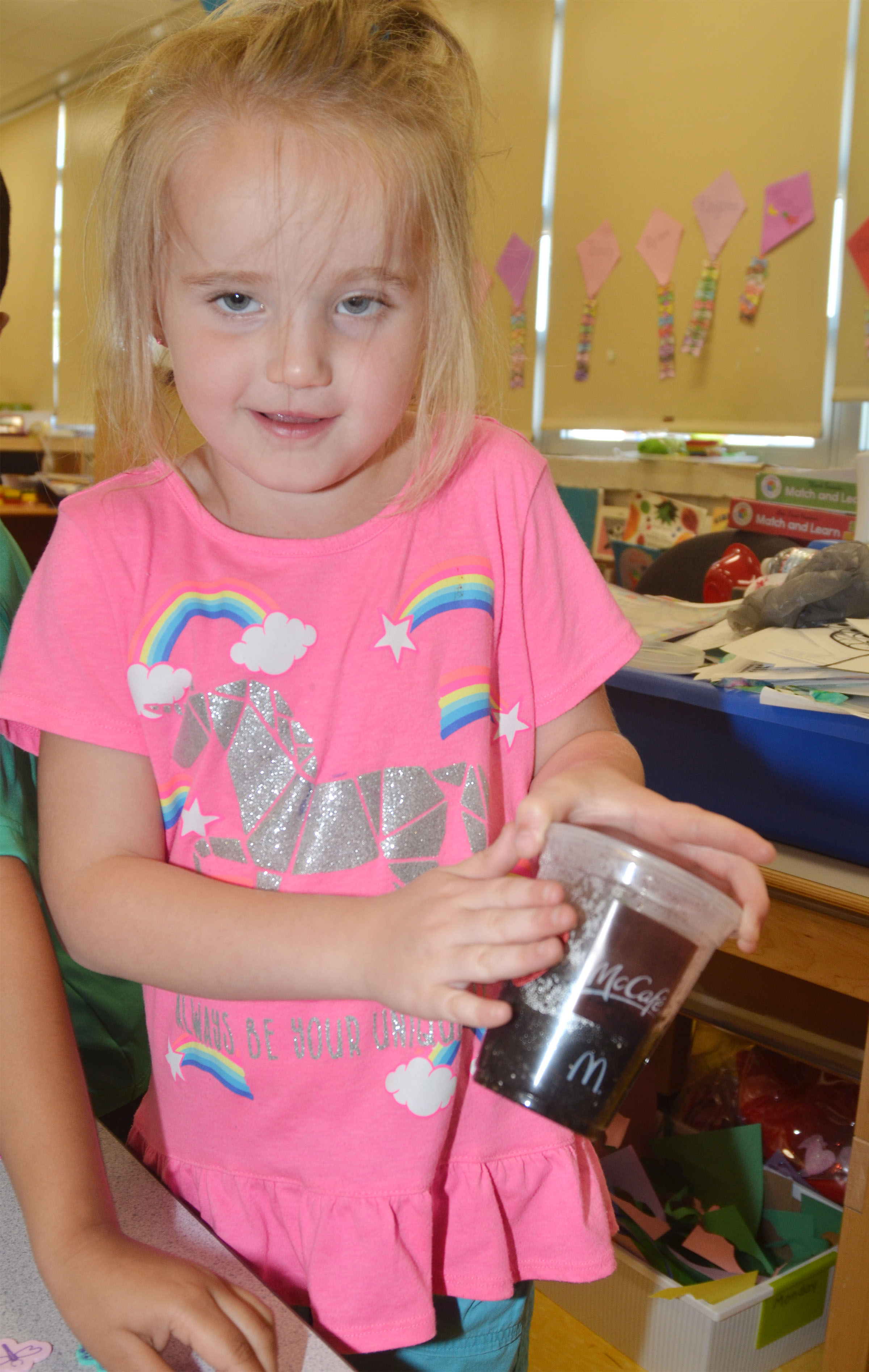 CES preschool student Trinity Dye decorates the cup in which she grew flowers for her mother.