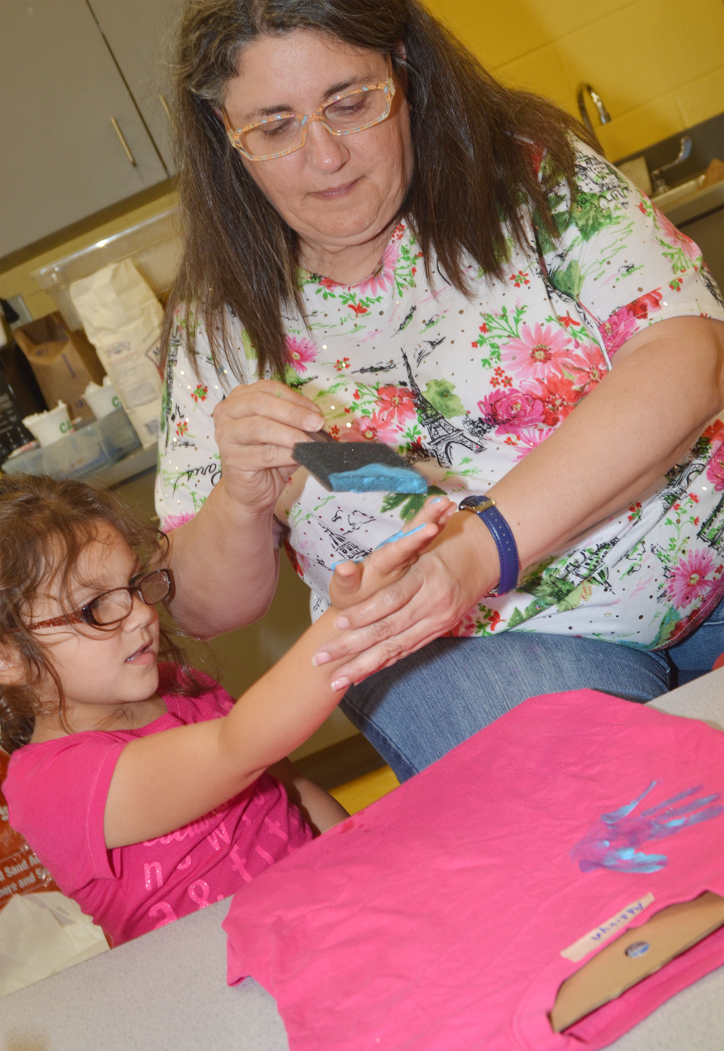CES preschool teacher Sherry Cowherd helps Addisyn Taylor make the t-shirt she will wear at the end of the year musical performance on Thursday, May 4.