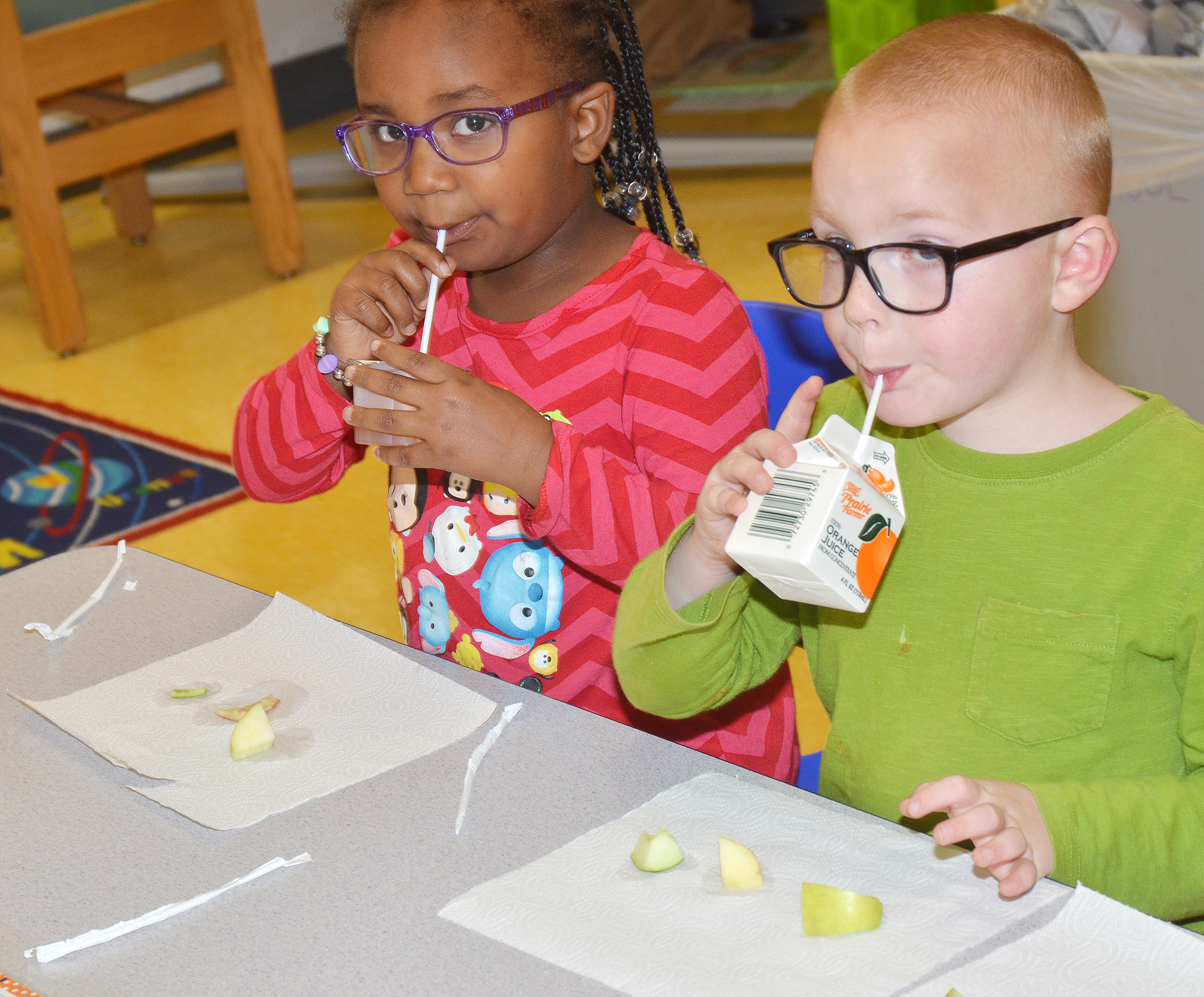 CES preschool students Kyona Mitchell, at left, and Anthony McClure enjoy their apples.