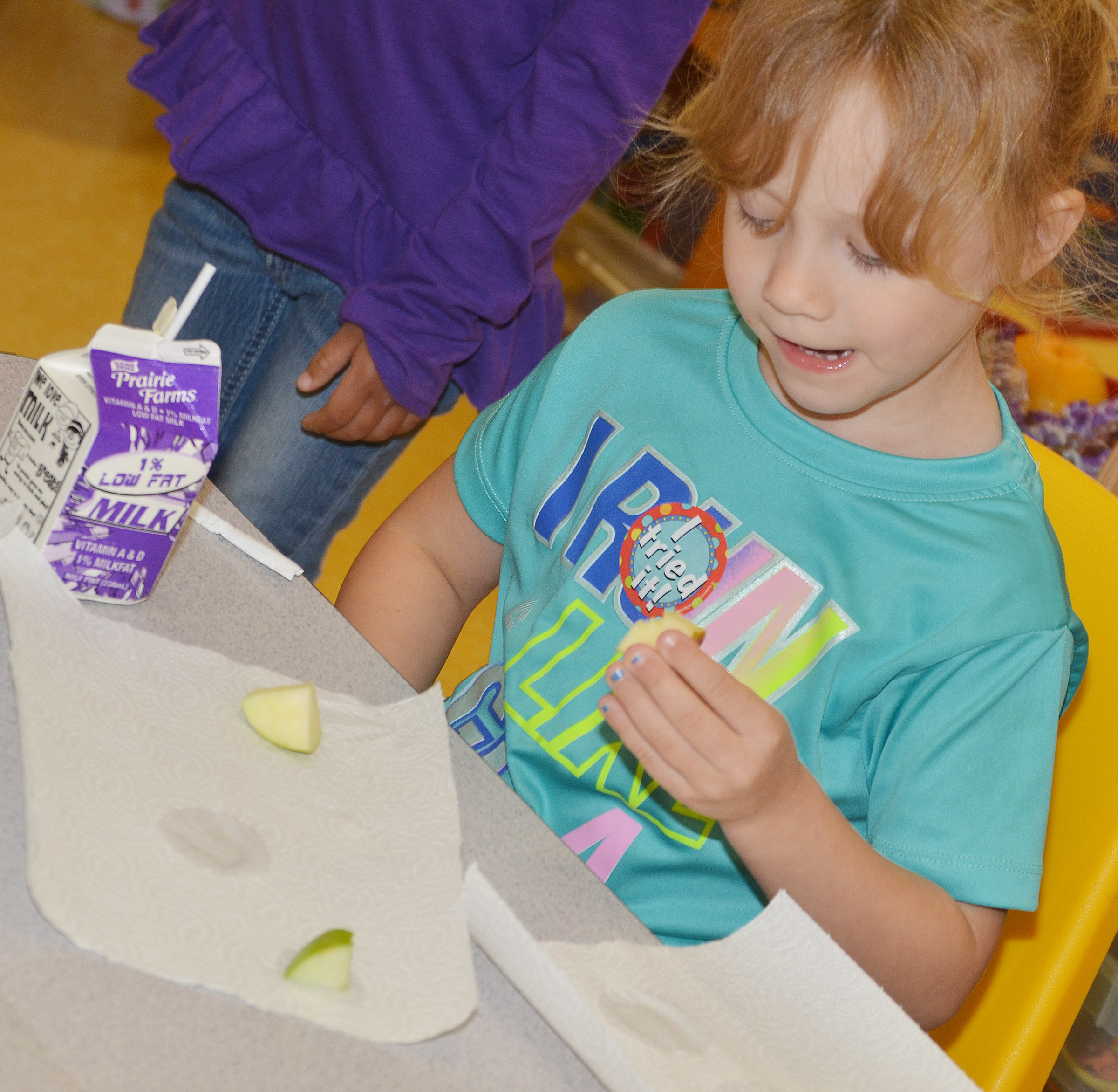 CES preschool student Aubree Hall samples an apple.