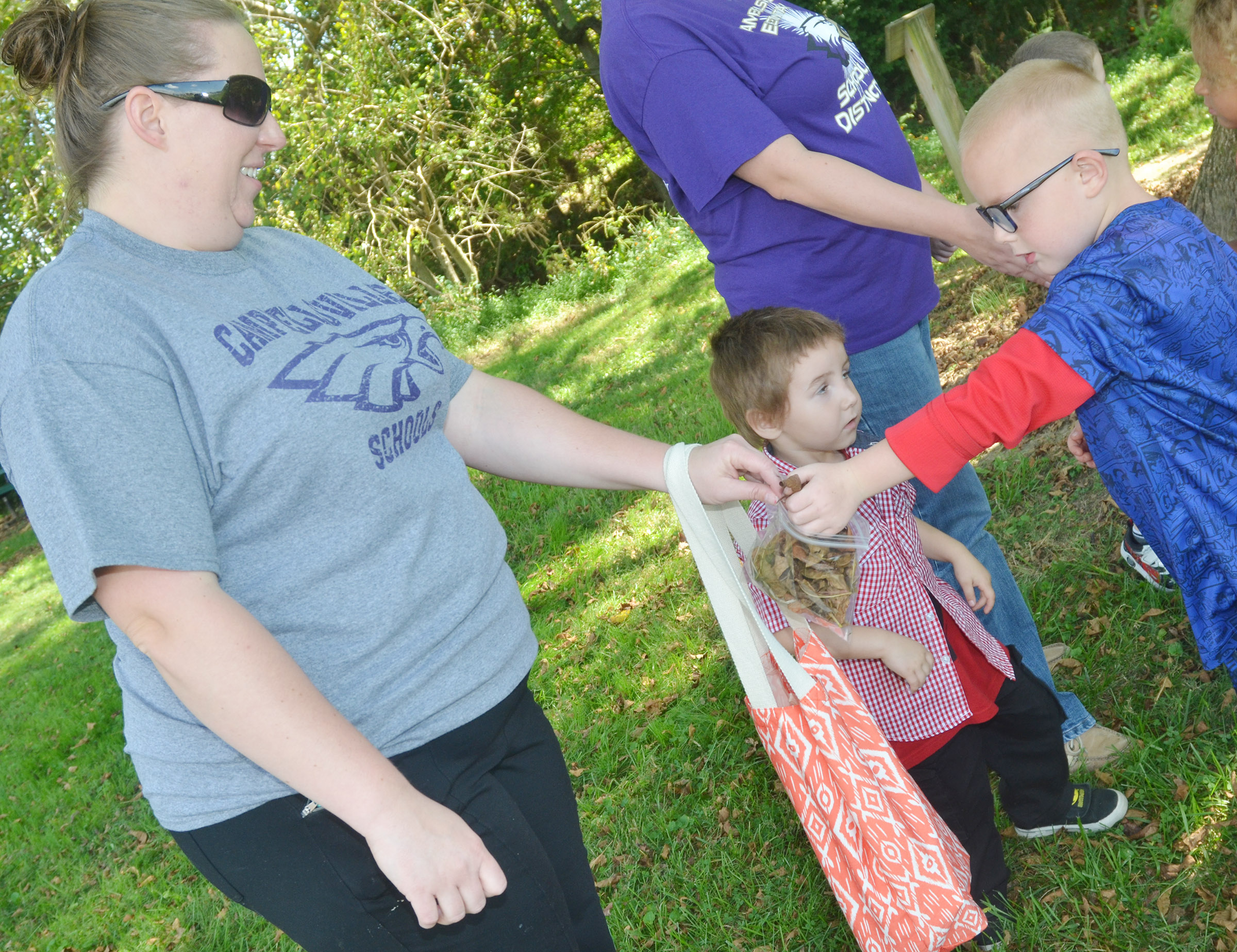 CES preschool teacher Julie Shelton collects leaves from student Anthony McClure.