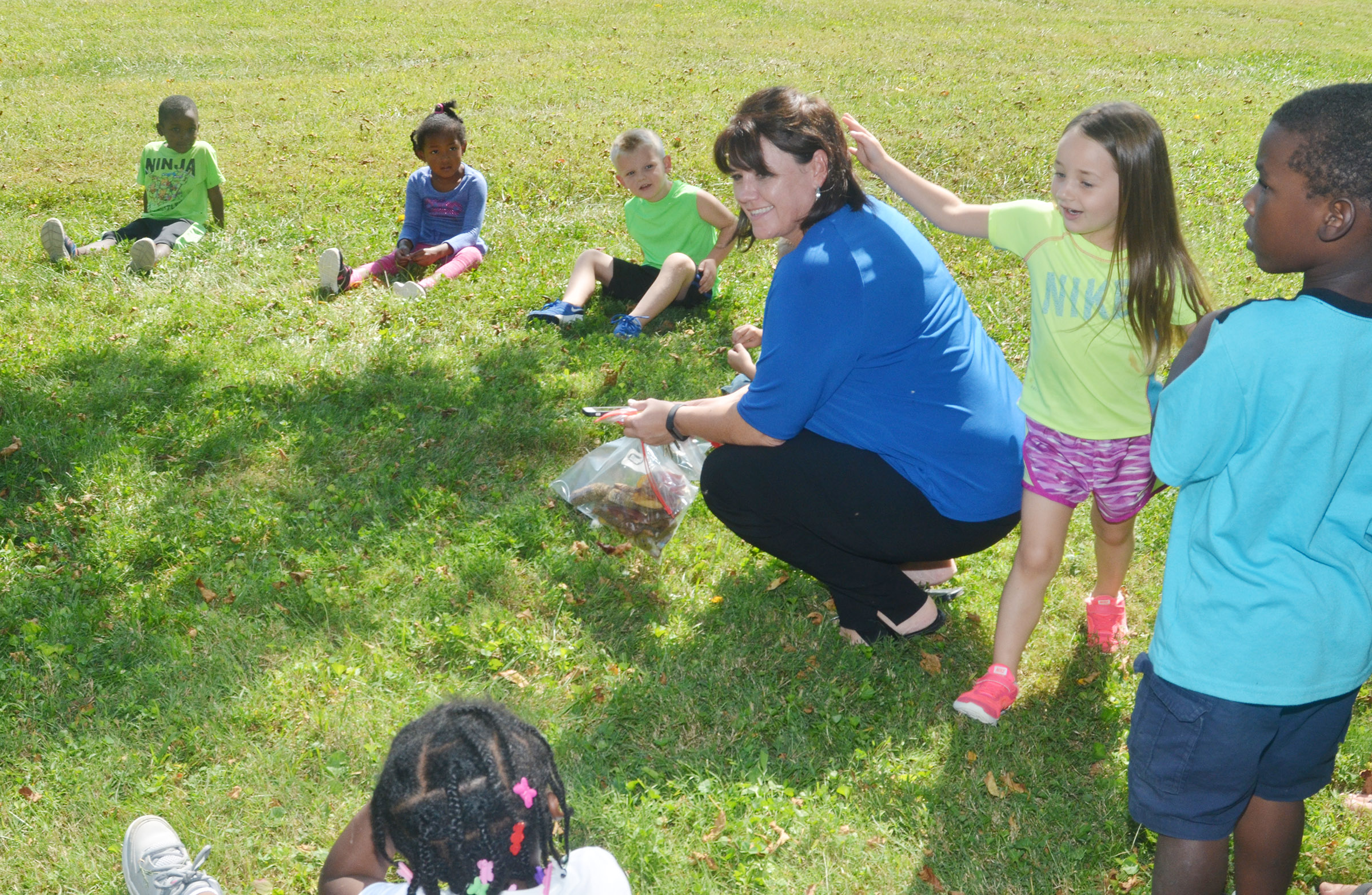 CES preschool student Lylah Davis plays Duck, Duck, Goose with her teacher Denise Spencer and her classmates.