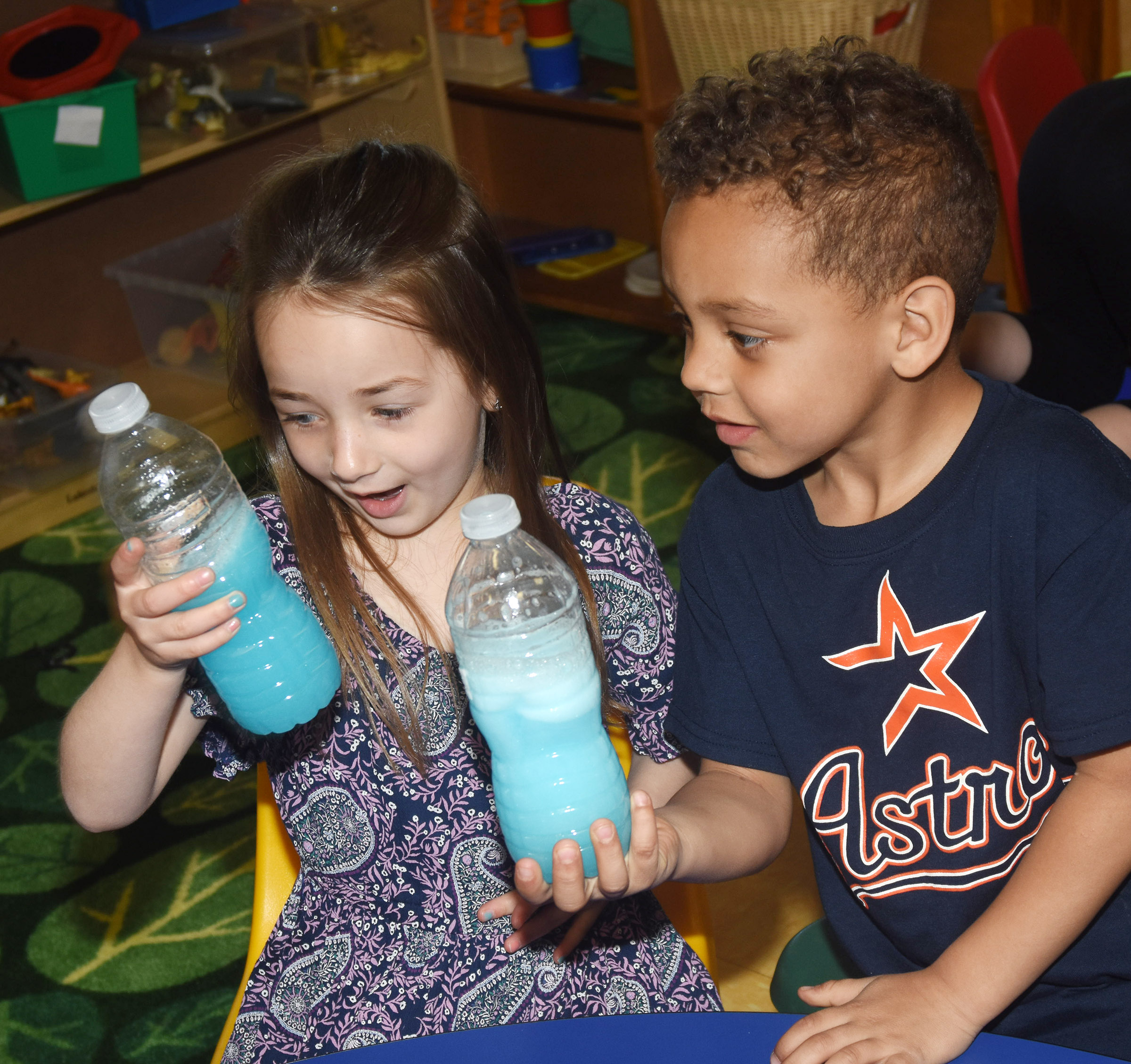 CES preschool students Lylah Davis, at left, and Jasiahas Anderson shake their oceans in a bottle.