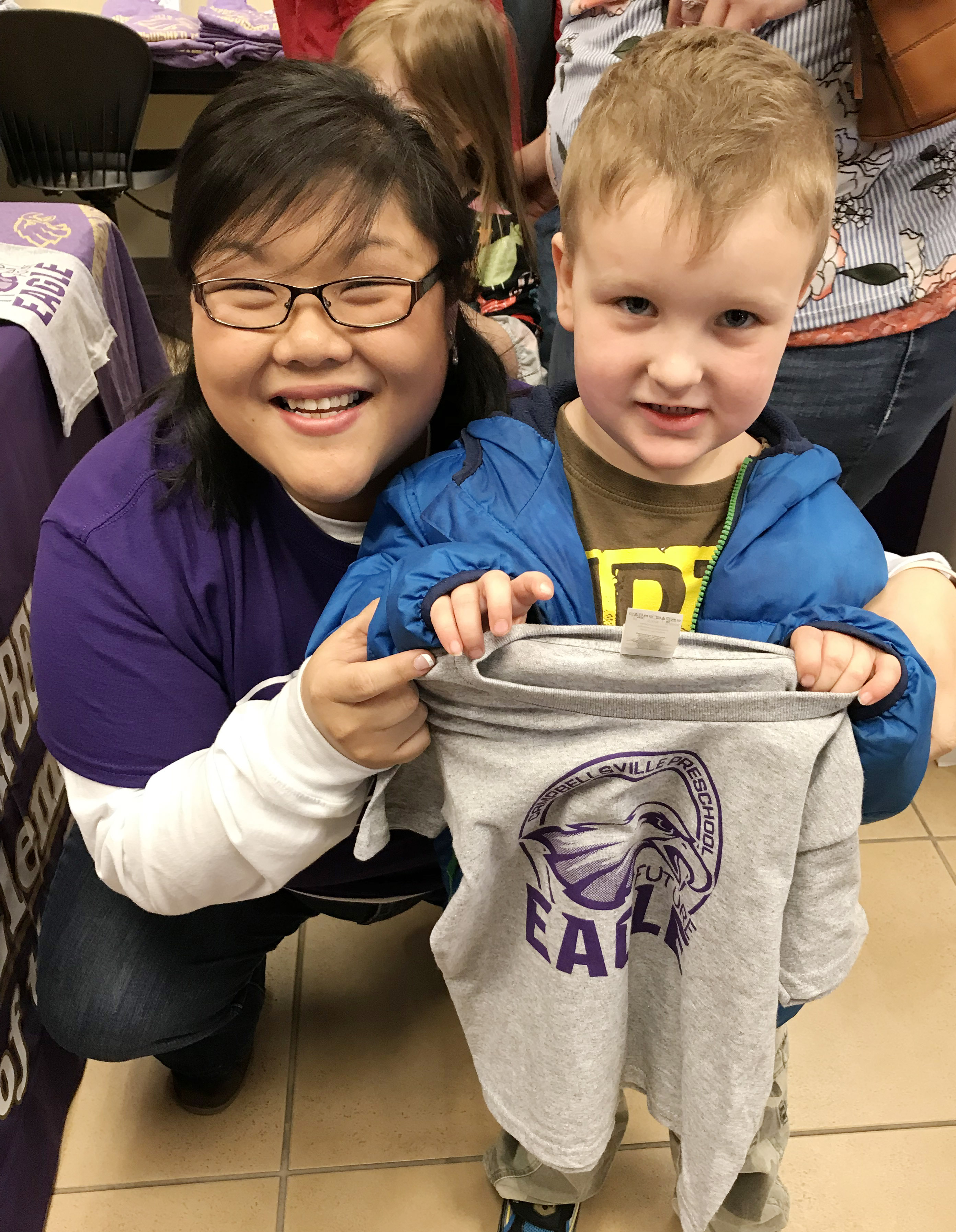 "CES preschool assistant Brittany Johnson poses for a photo with her student Gannon Scott, holding his ""Future Eagle"" t-shirt."