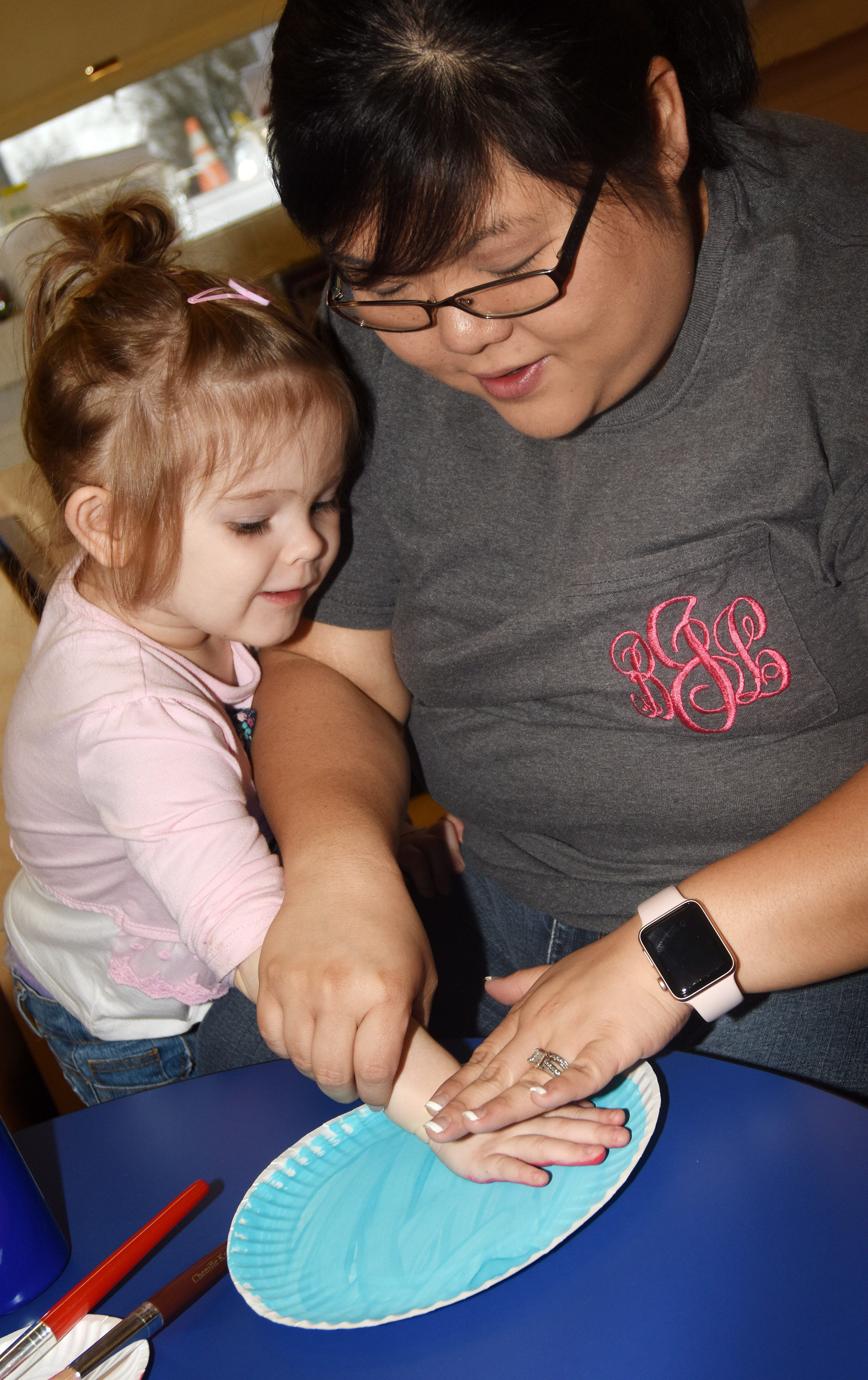 CES preschool assistant Brittany Johnson helps Julie Lasater paint her red fish and blue fish.