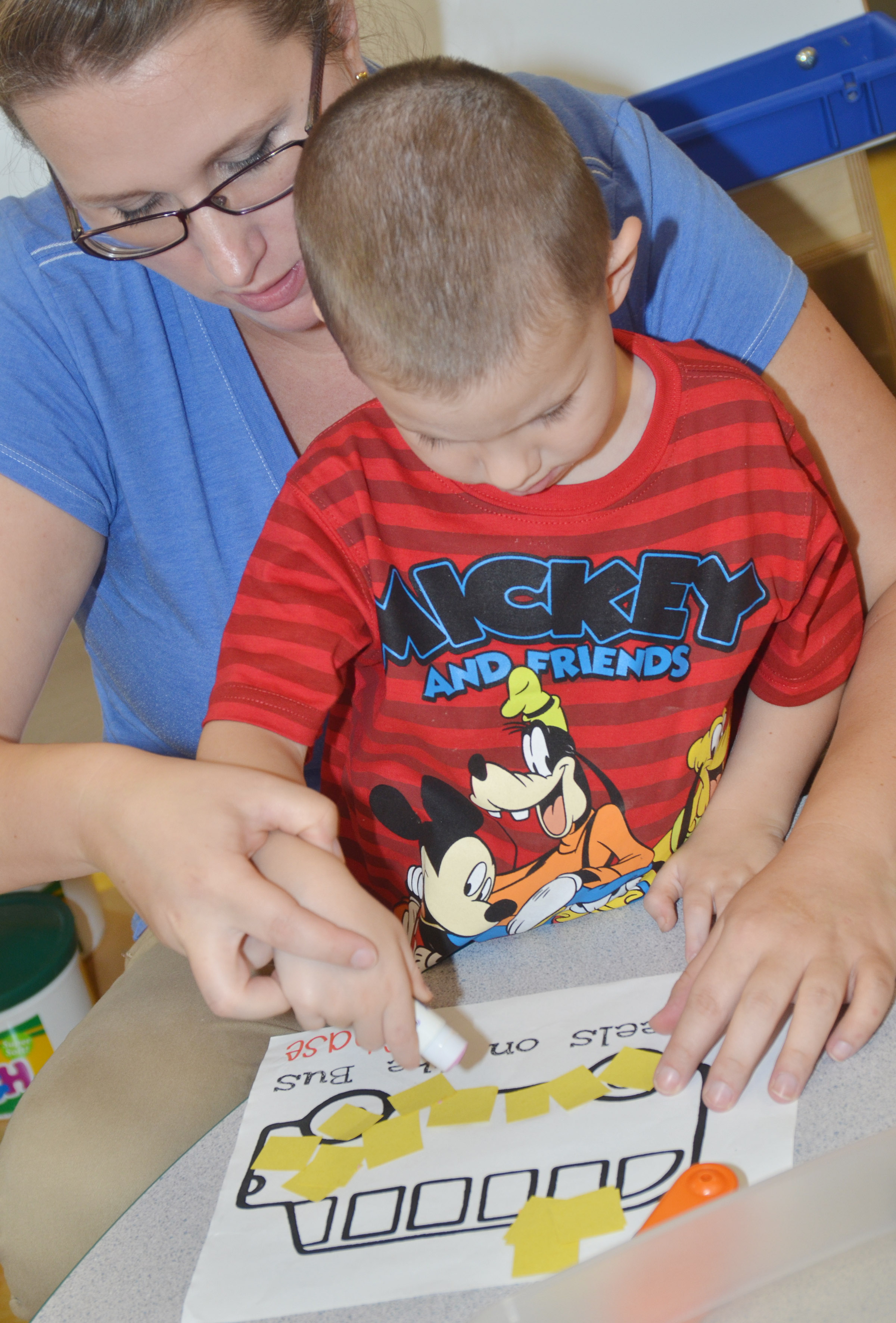 CES preschool student Chase Arnett glues construction paper on his school bus, with help from preschool assistant Jessica Williams.