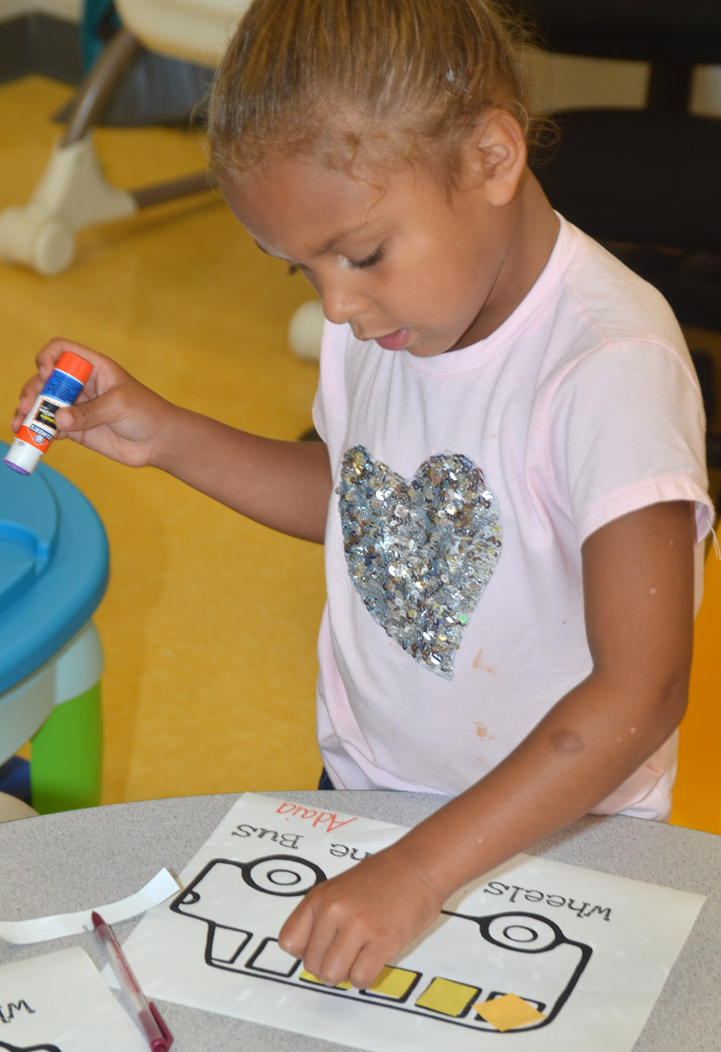 CES preschool student Adaia Taylor glues construction paper on her school bus.