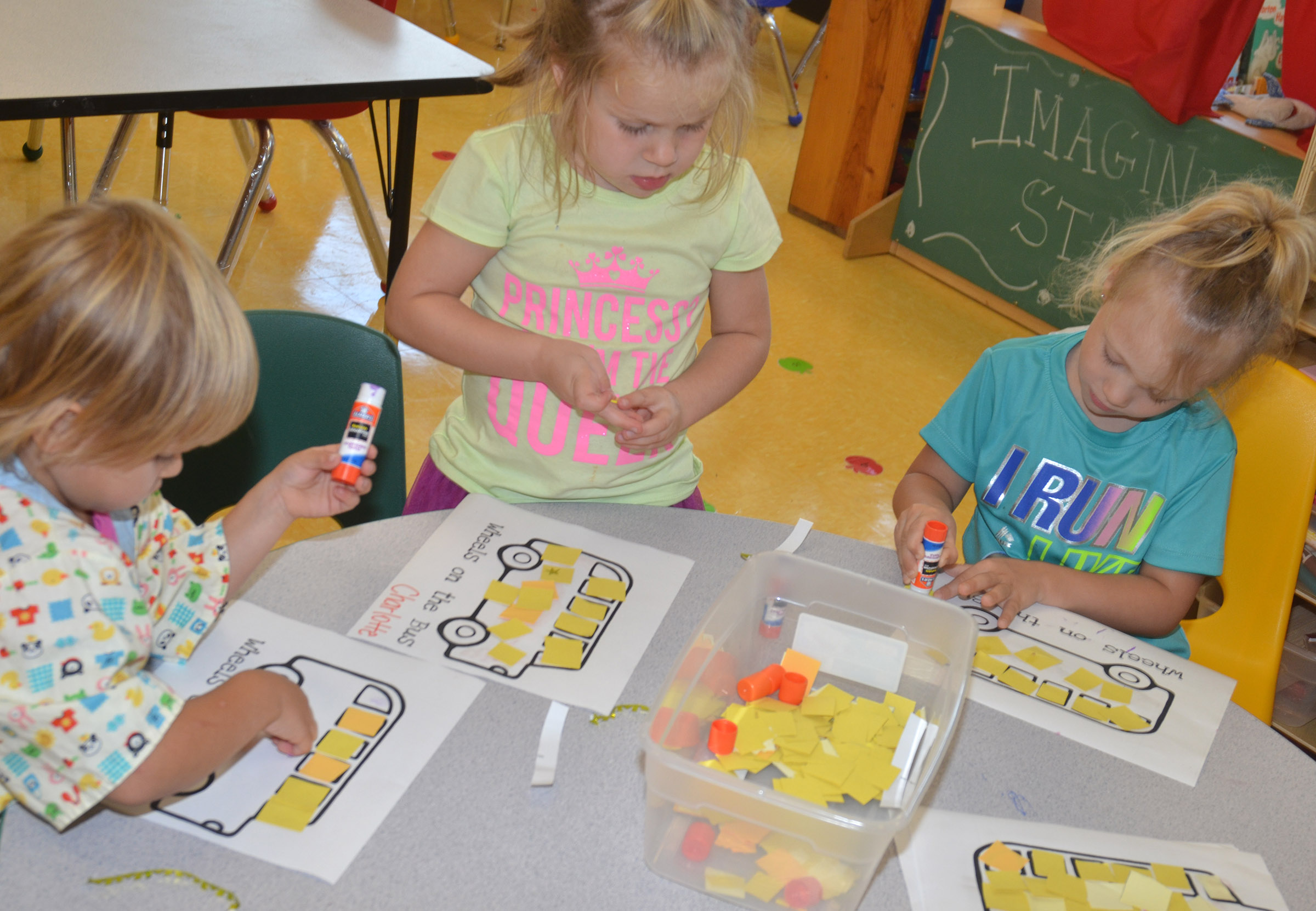 From left, CES preschool students Elliana Morton, Charlotte Hoots and Aubree Hall decorate their school buses.