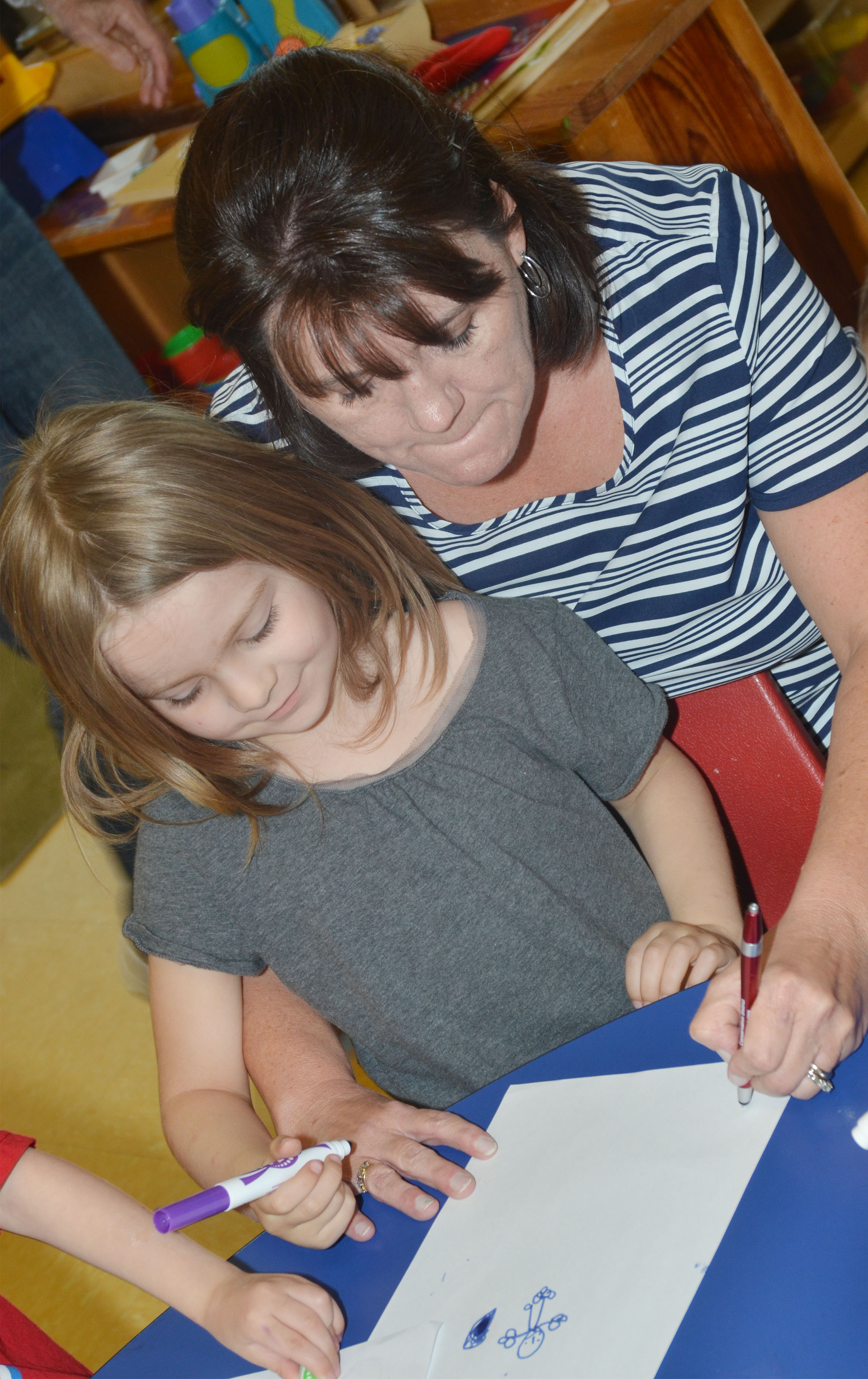 CES preschool teacher Denise Spencer helps Daisy Rakes write about her favorite part of school.