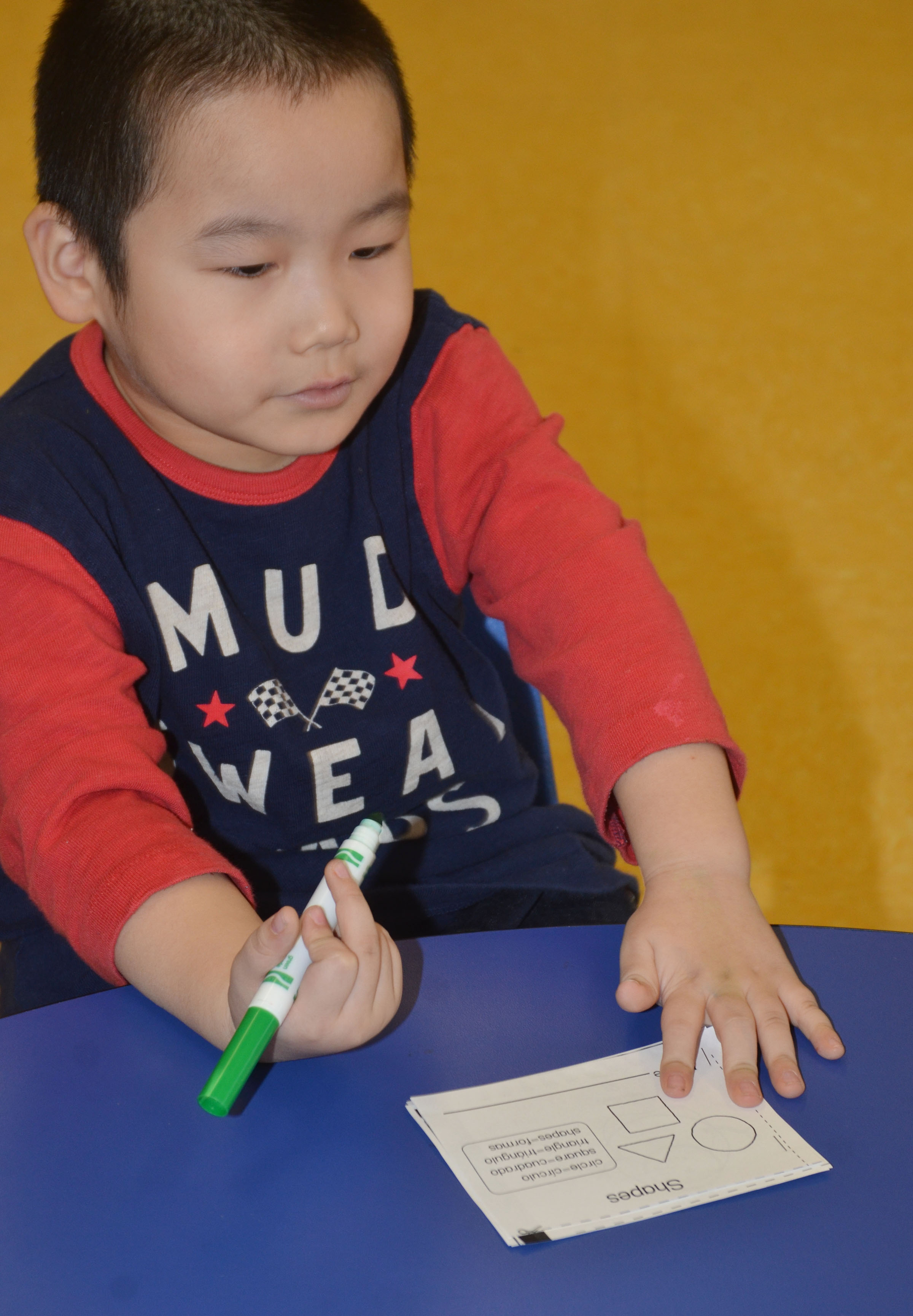 CES preschool student Calvin Yang colors in his shape booklet.