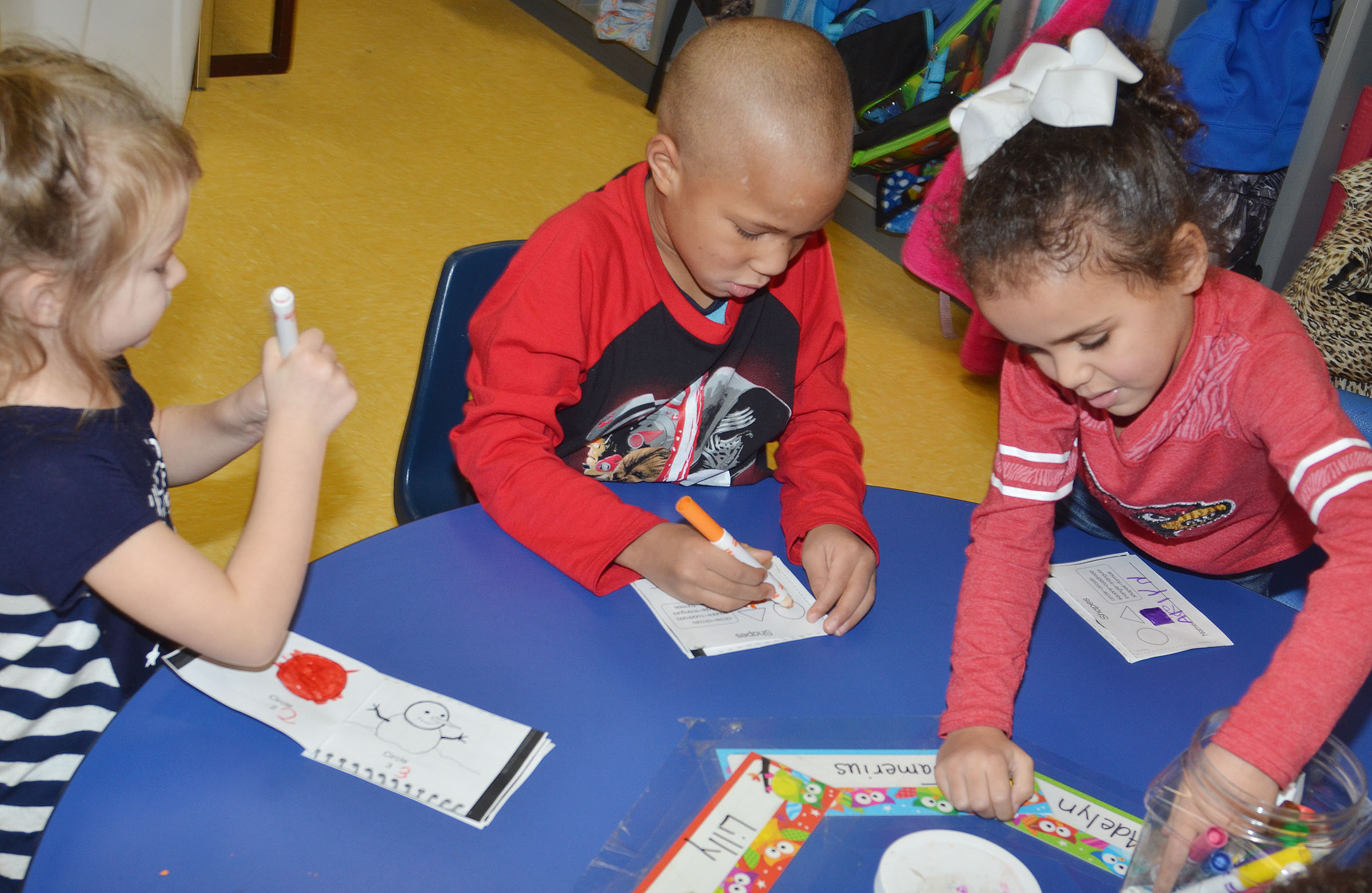 From left, CES preschool students Lilly Spencer, Jamerius Miller and Adelyn Litsey color in their shape booklets.