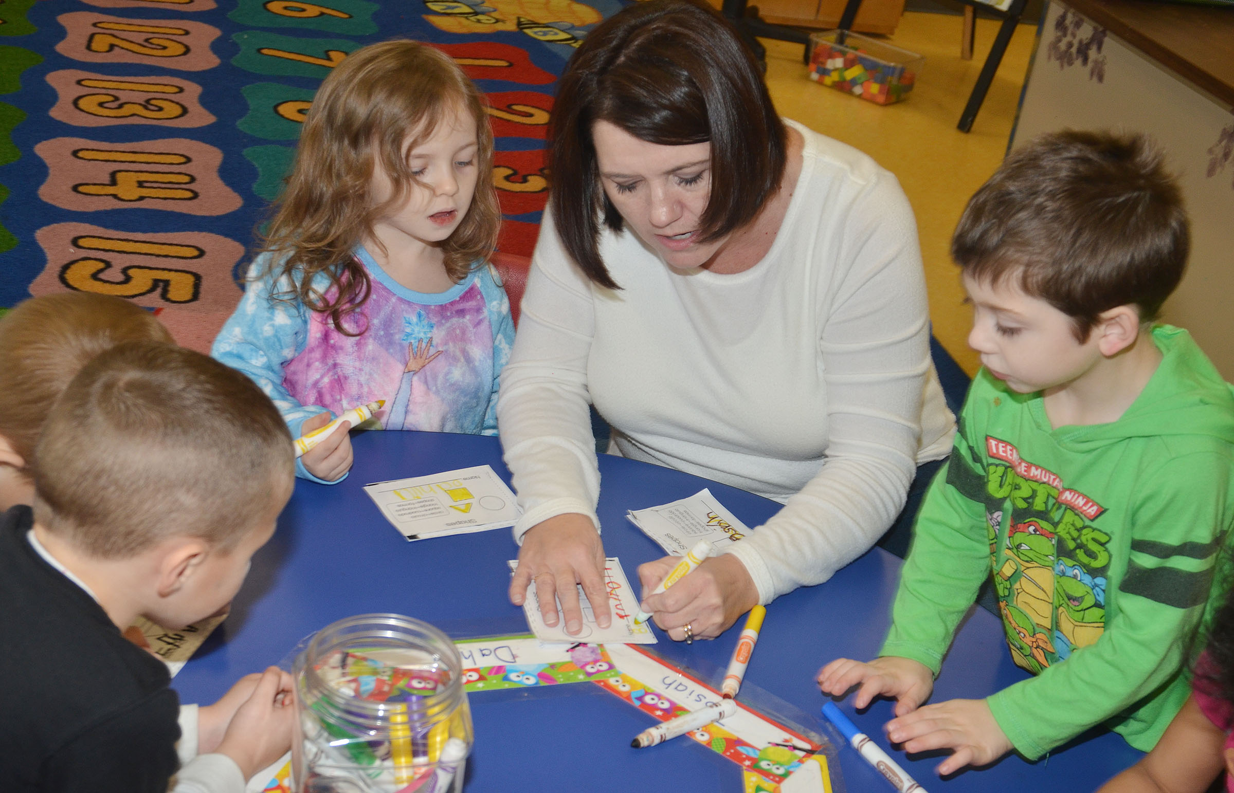 CES preschool teacher Denise Spencer helps students Dahlia Ward, at left, and Josiah Dean color their shapes.