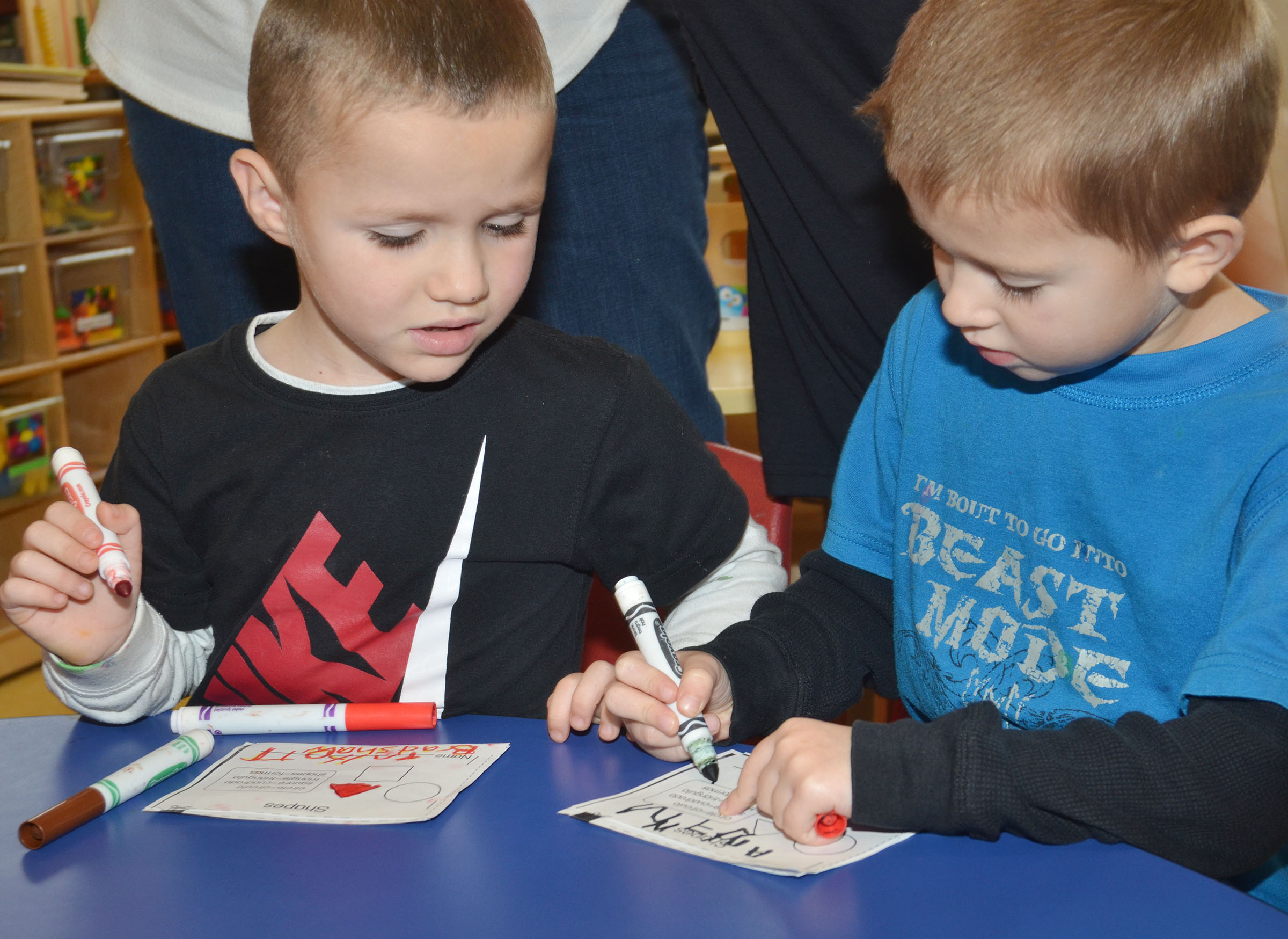 CES preschool students Triton Bradshaw, at left, and Andrew Stout write their names on their shape booklets.