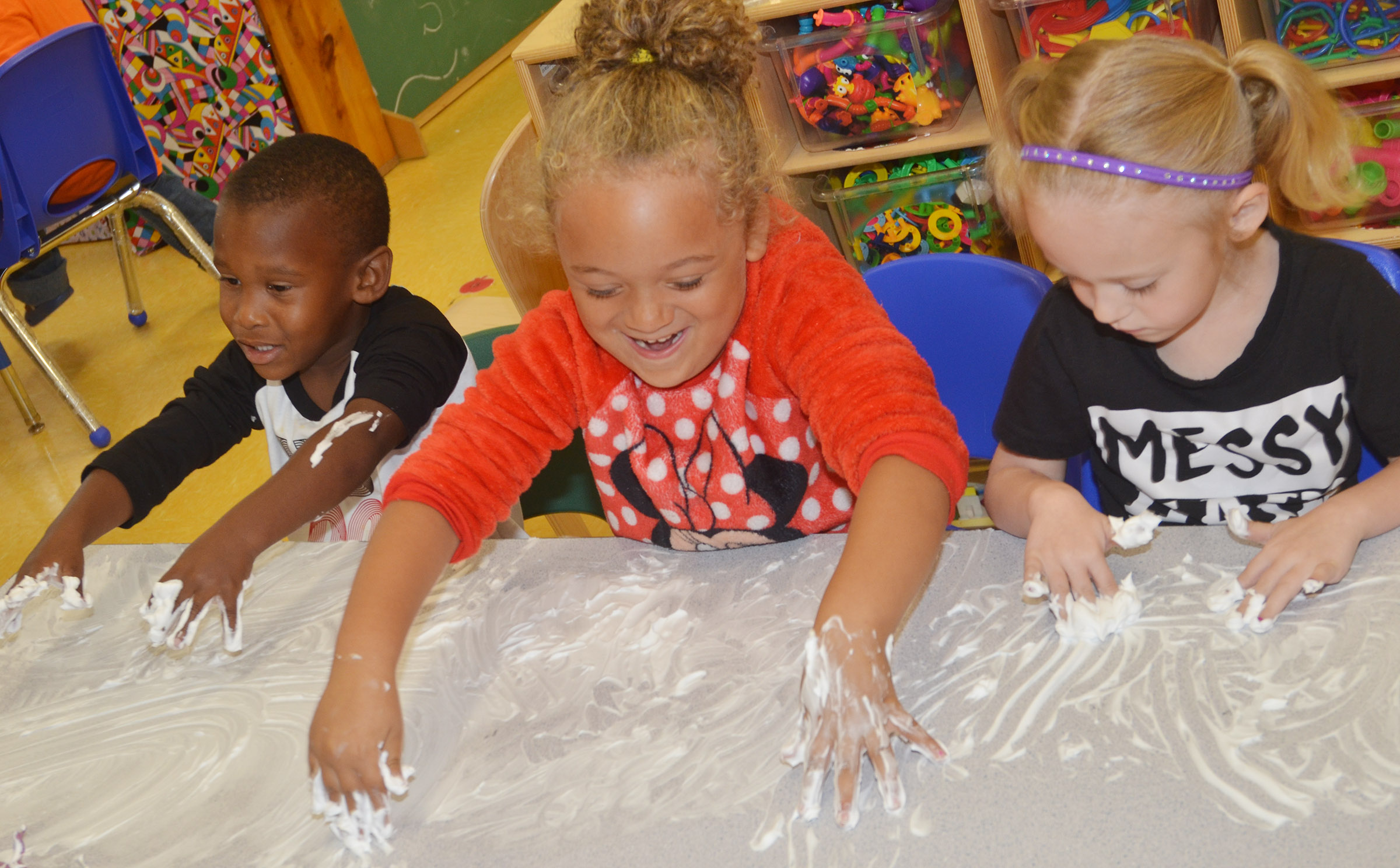 From left, CES preschool students Mason Conner, Layla Barbee and Kylie Thompson draw in their shaving cream.