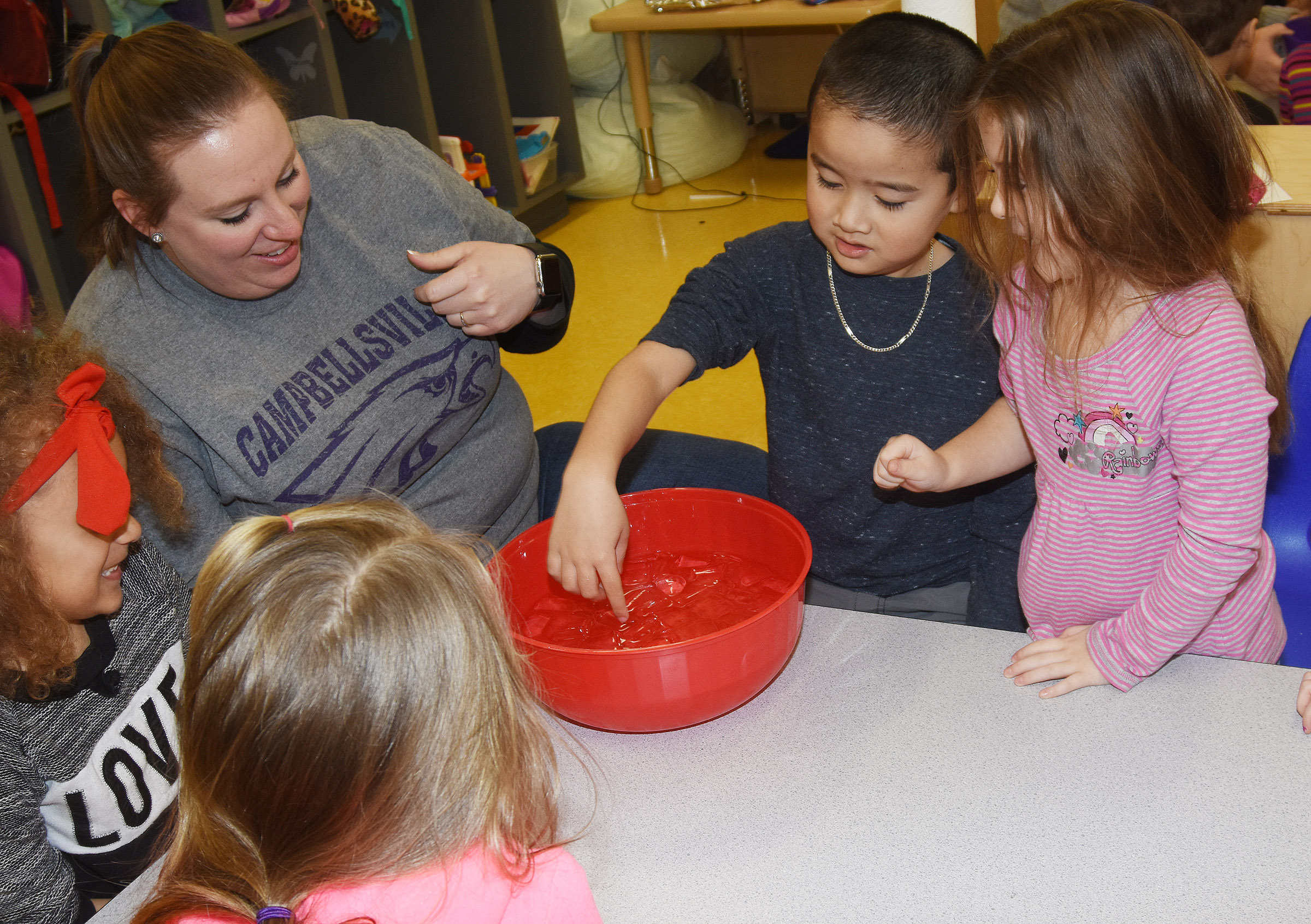 CES preschool student Minh Turdo places his hand inside ice water to see how cold it is, as his classmates and teacher Julie Shelton watch.