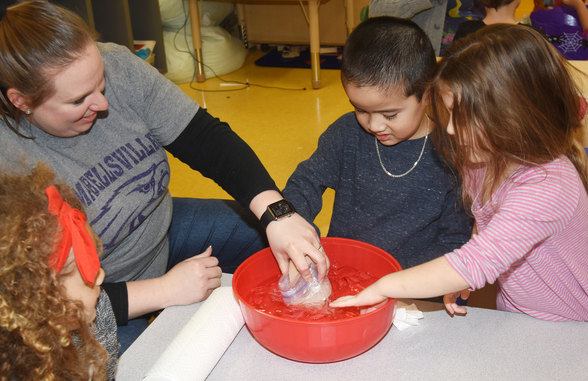 CES preschool teacher Julie Shelton helps Minh Turdo place his hand inside a bag of blubber to see how it keeps an animal warm in the winter. At right is Mila Moss.