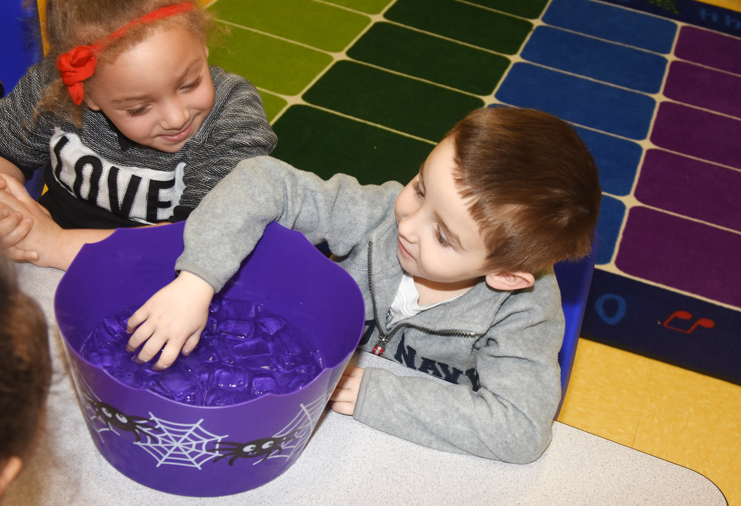 CES preschool student Noelan McMahan places his hand inside ice water to see how cold it is, as his classmate Jayla Barbee watches.