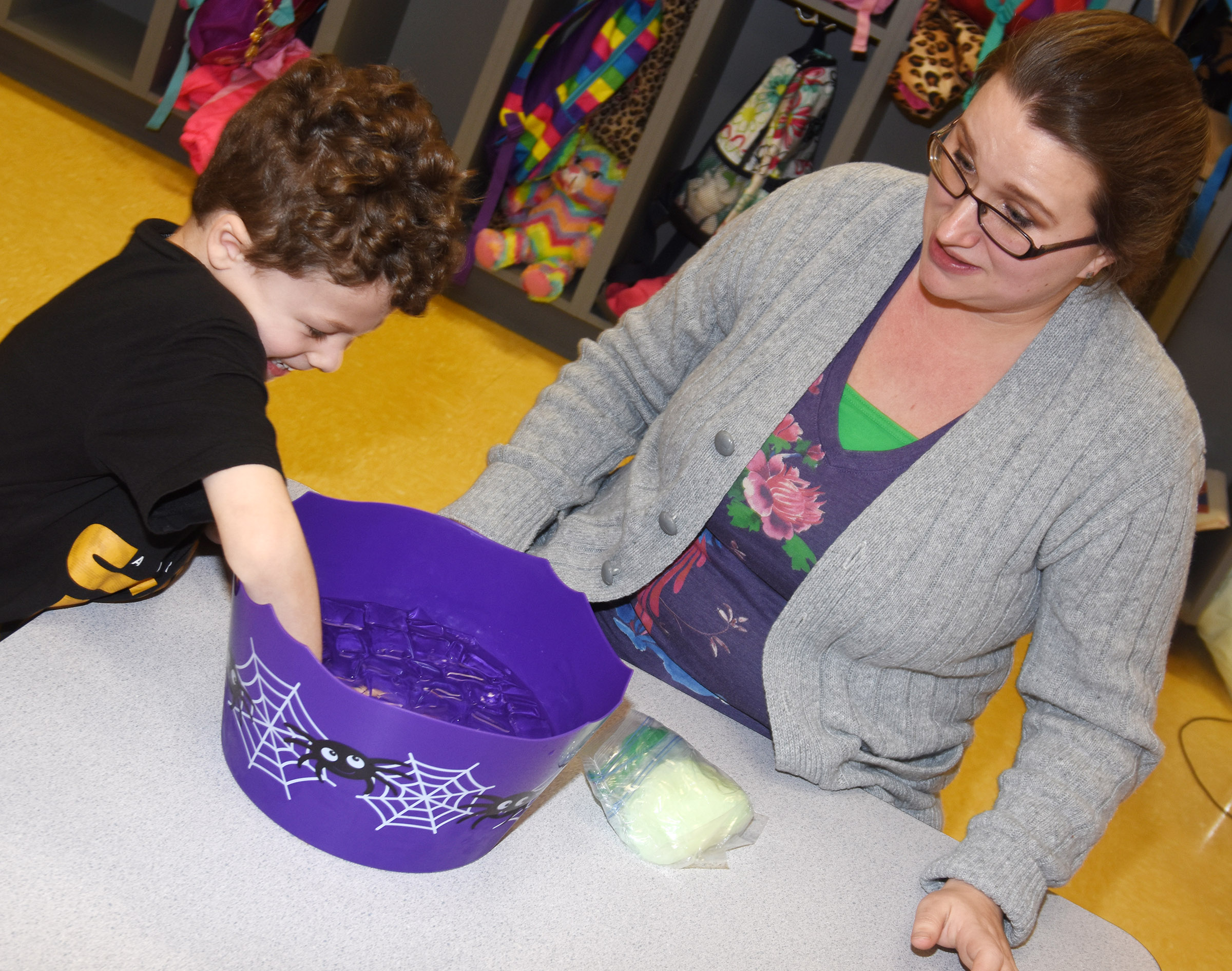 CES preschool assistant Jessica Williams watches as Zyron Young places his hand inside ice water.