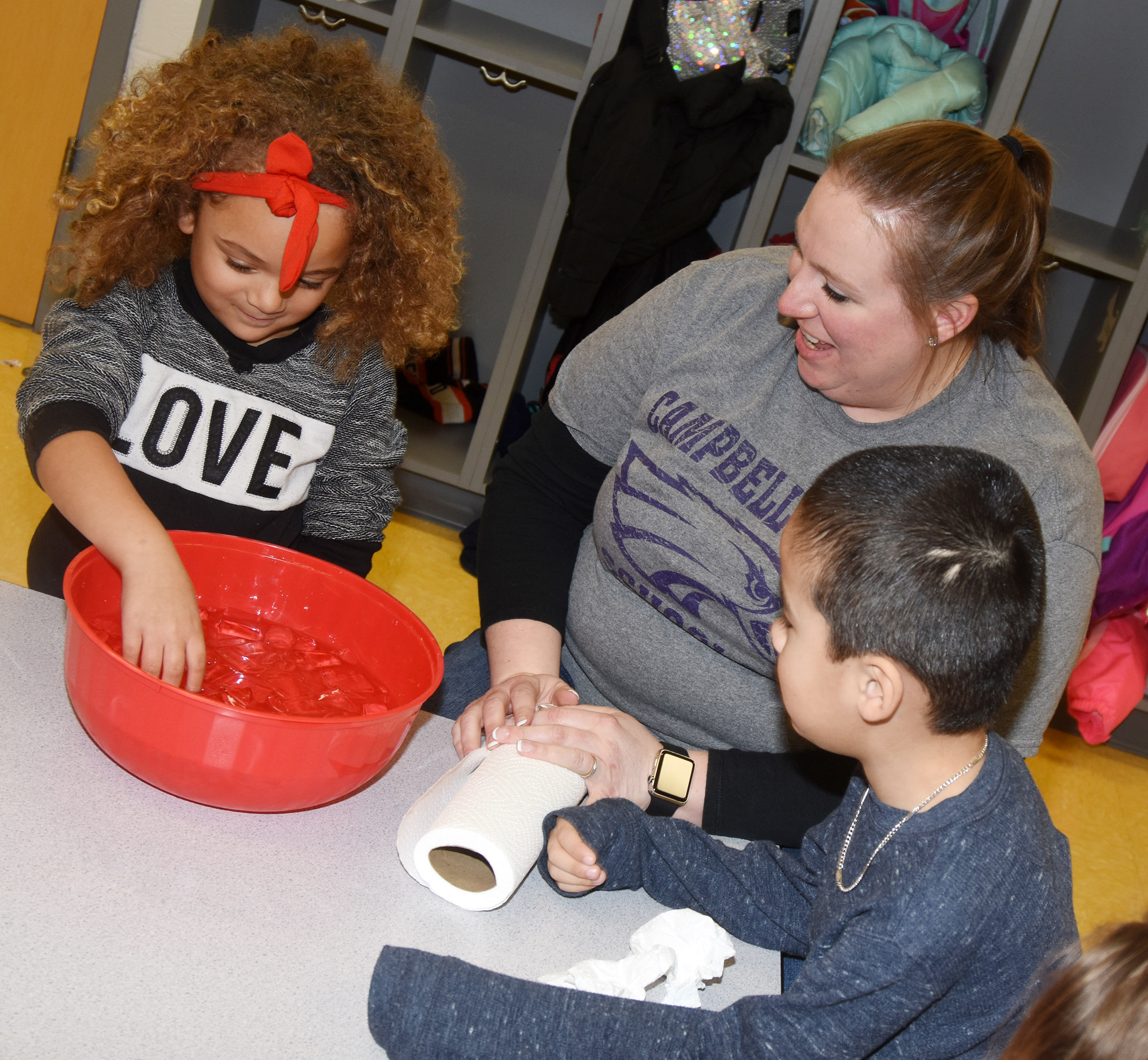 CES preschool student Layla Barbee places her hand inside ice water to see how cold it is, as classmate Minh Turdo and teacher Julie Shelton watch.