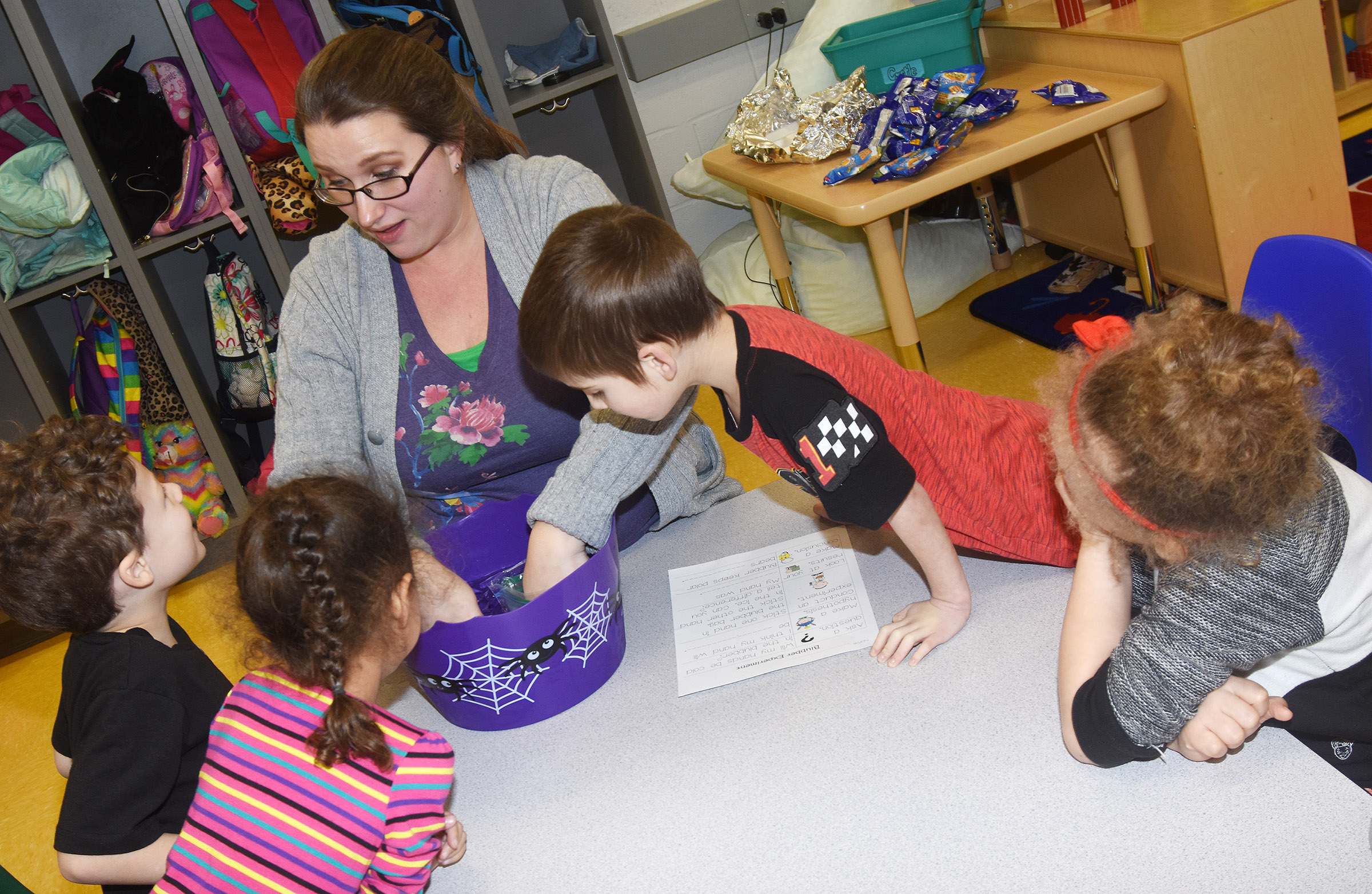 CES preschool assistant Jessica Williams places her hand inside ice water to see how cold it is, as her students watch.