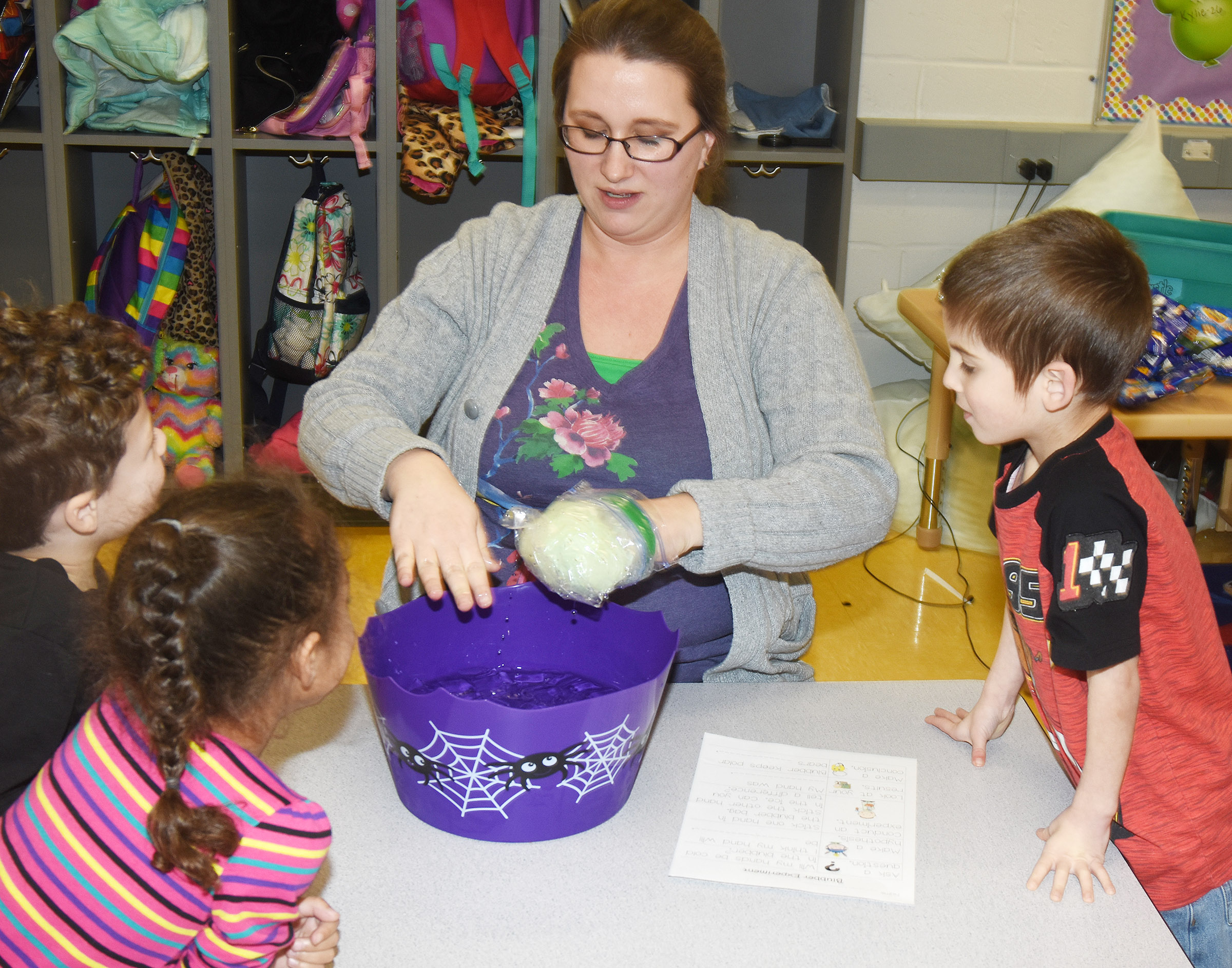 CES preschool assistant Jessica Williams places one hand inside a bowl of ice water and the other in a bag of blubber, to see how the blubber keeps animals warm in the winter.