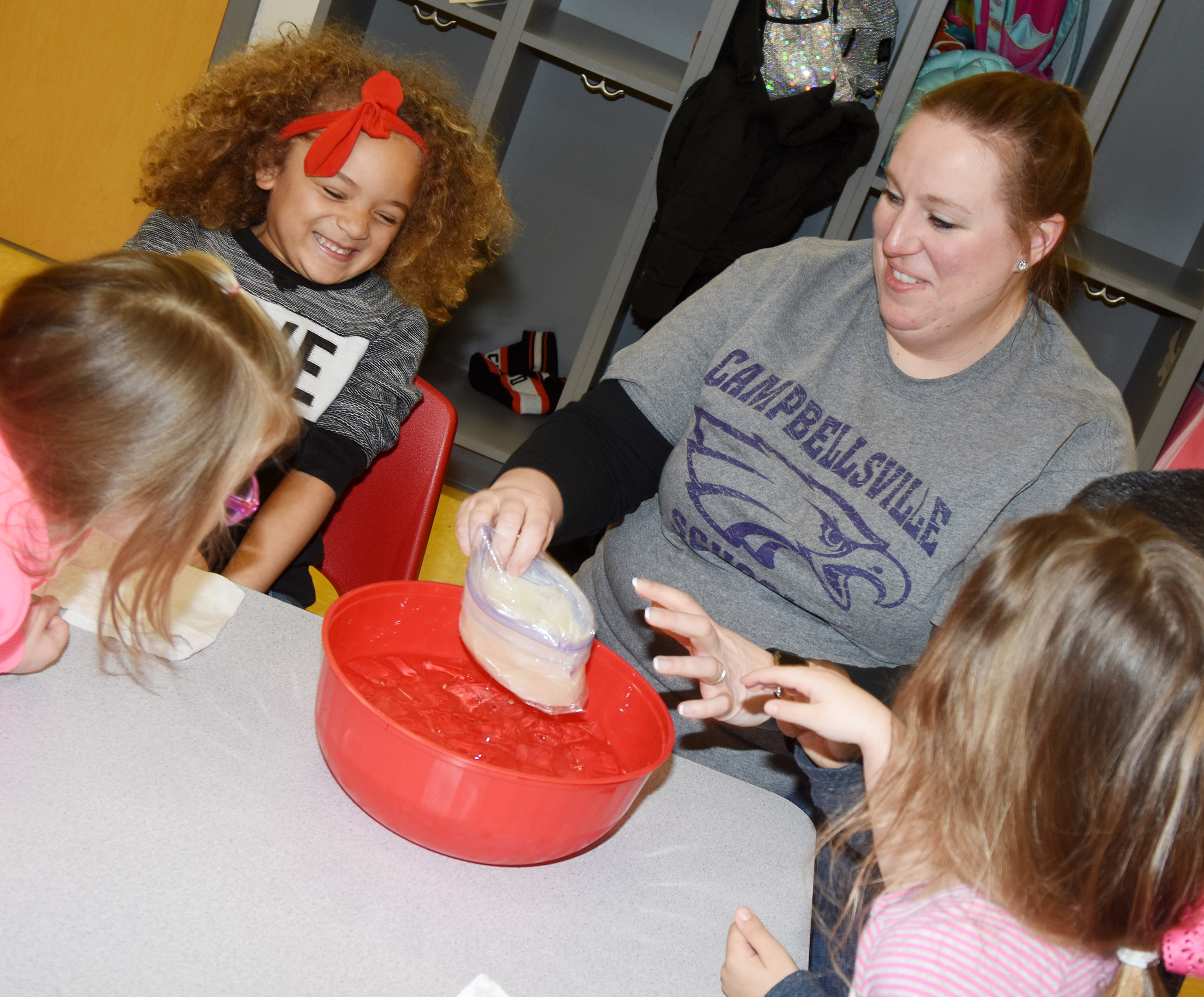 CES preschool teacher Julie Shelton shows her students how blubber can keep an animal warm in the winter.