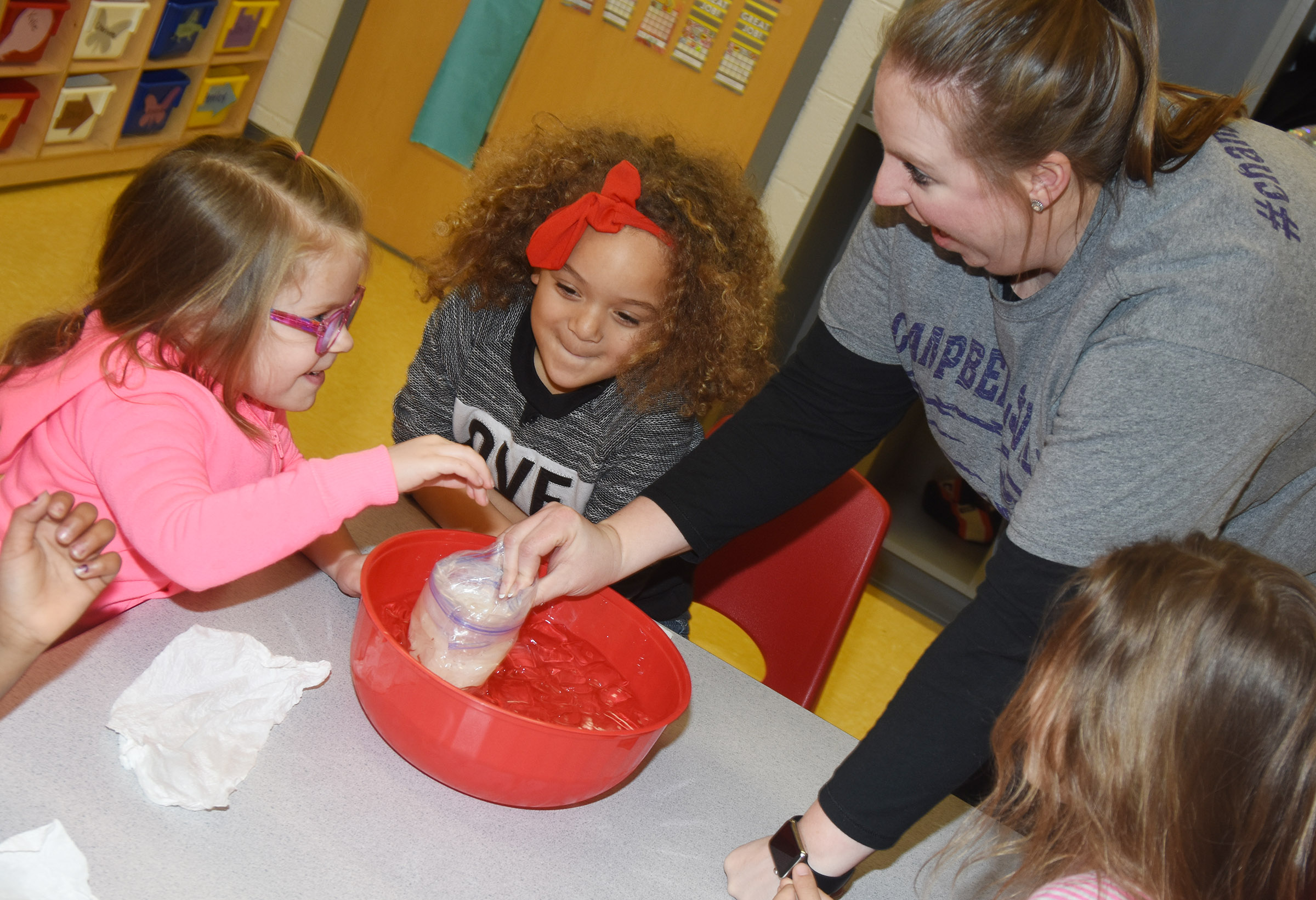 CES preschool student Charlotte Coots places her hand inside a bag of blubber so she can see how it keeps animals warm in the winter. Watching are classmate Layla Barbee, teacher Julie Shelton and classmate Mila Moss.