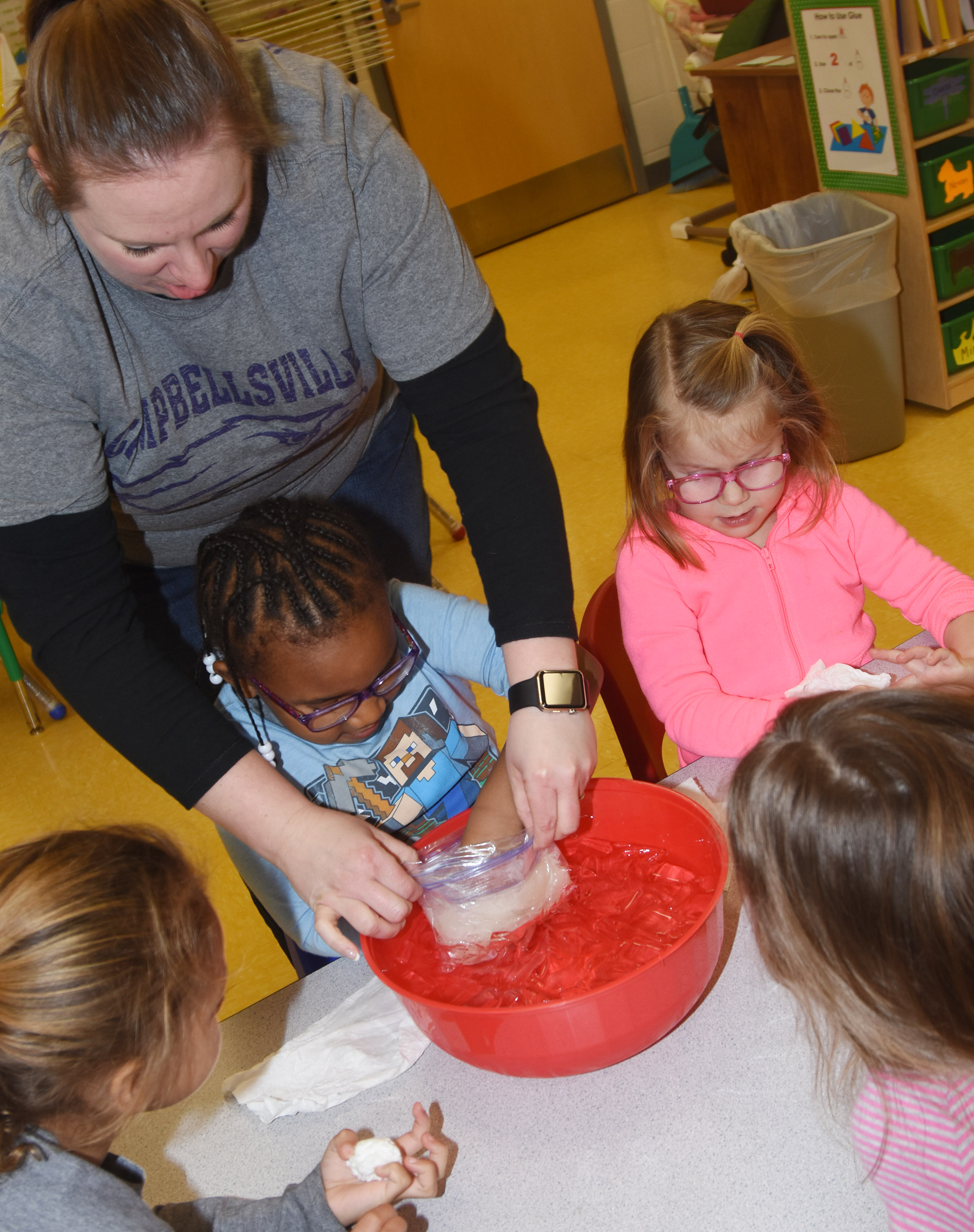 With some help from her teacher Julie Shelton, CES preschool student Kyona Mitchell places her hand inside a bag of blubber to see how it keeps an animal warm in the winner.