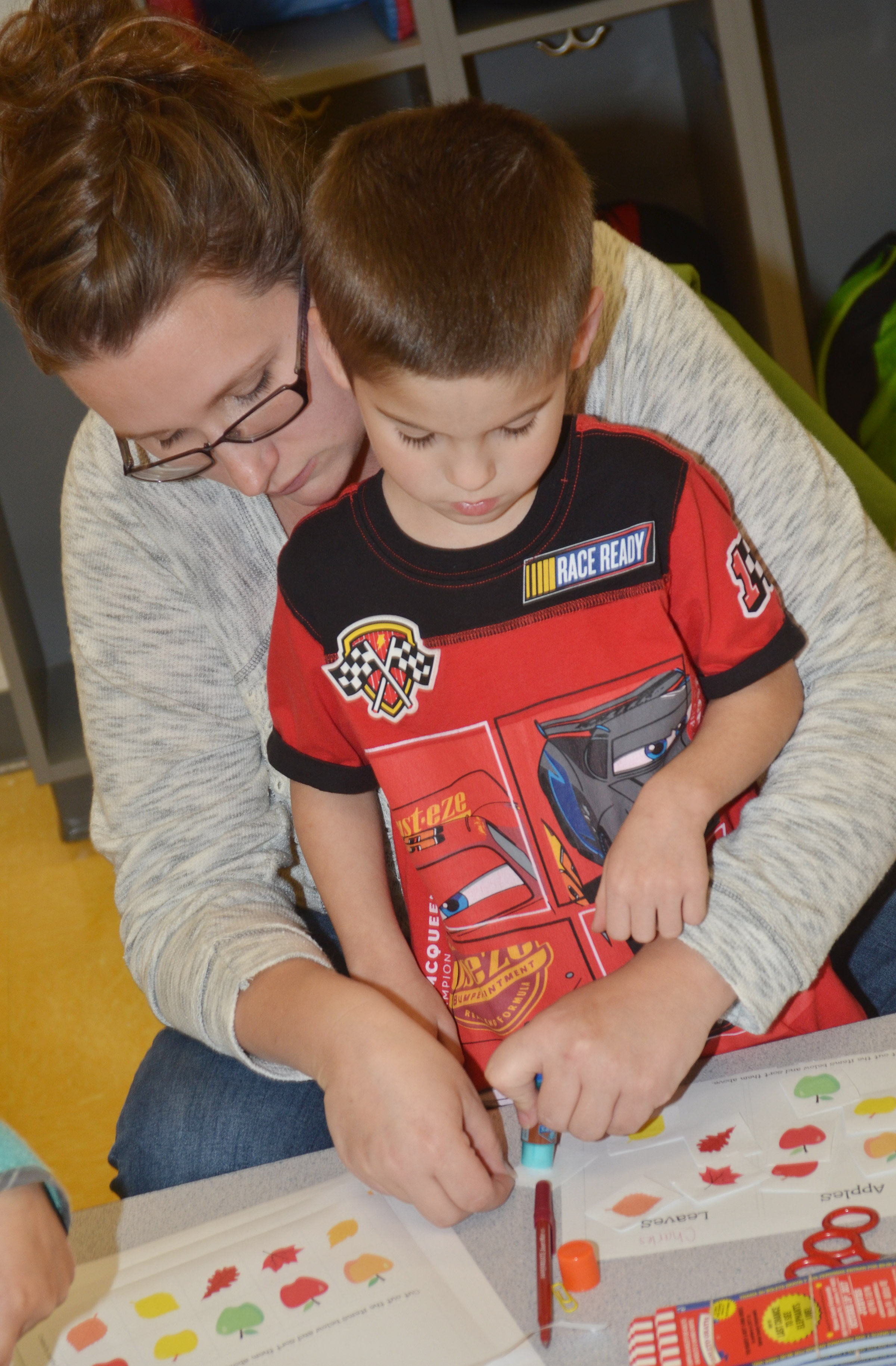 CES preschool assistant Jessica Williams helps Charlie Woodbury sort his apples and leaves by color.