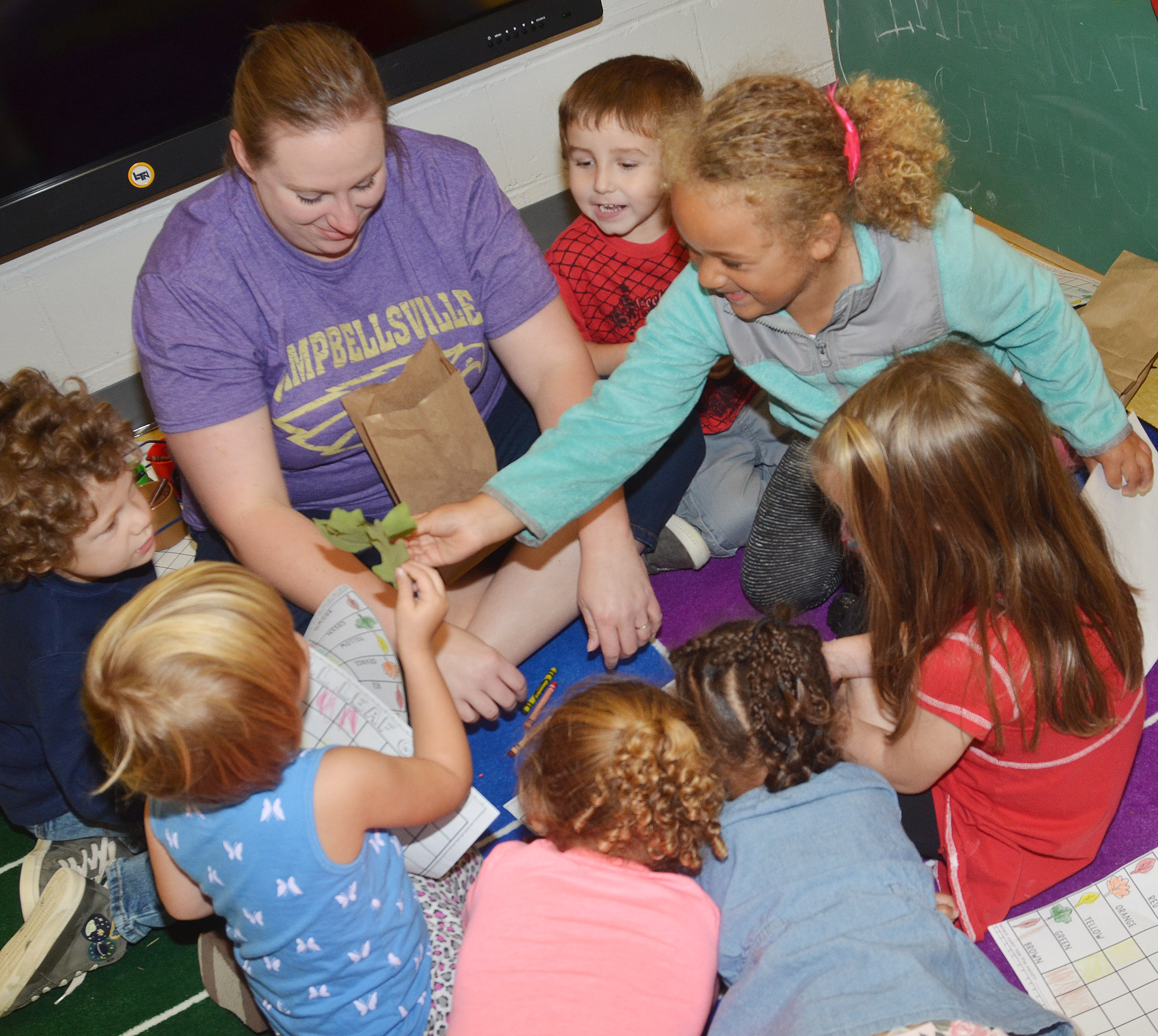CES preschool teacher Julie Shelton and her students see how many leaves they have of each color.