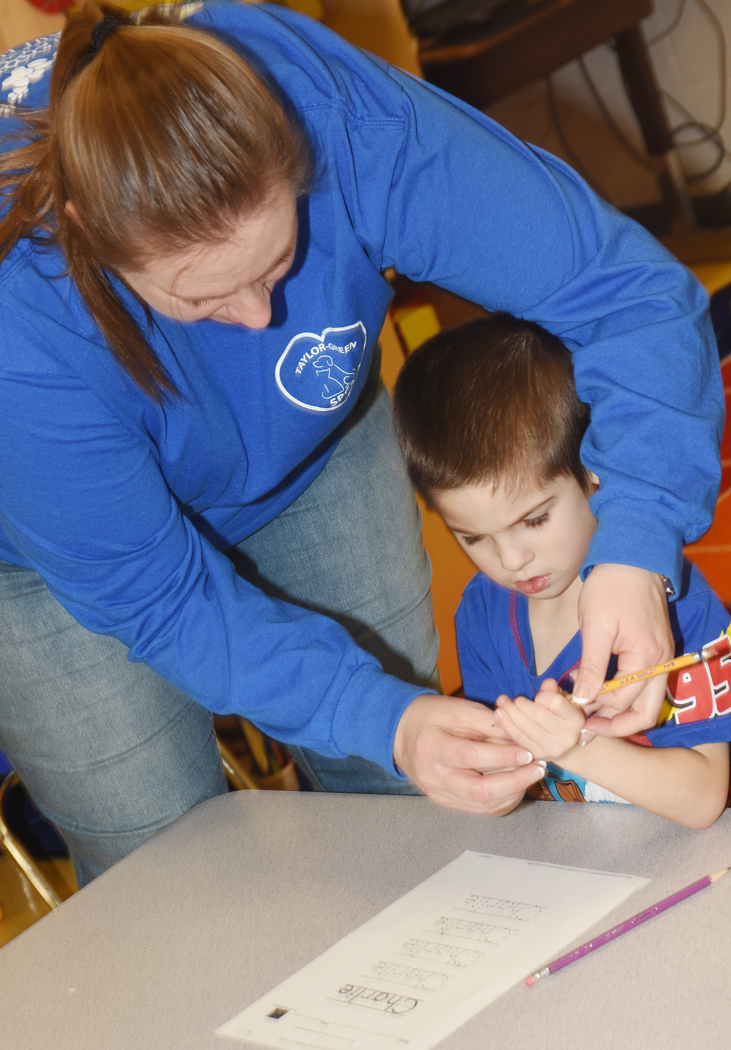 CES preschool teacher Julie Shelton helps Charlie Woodbury write his name.