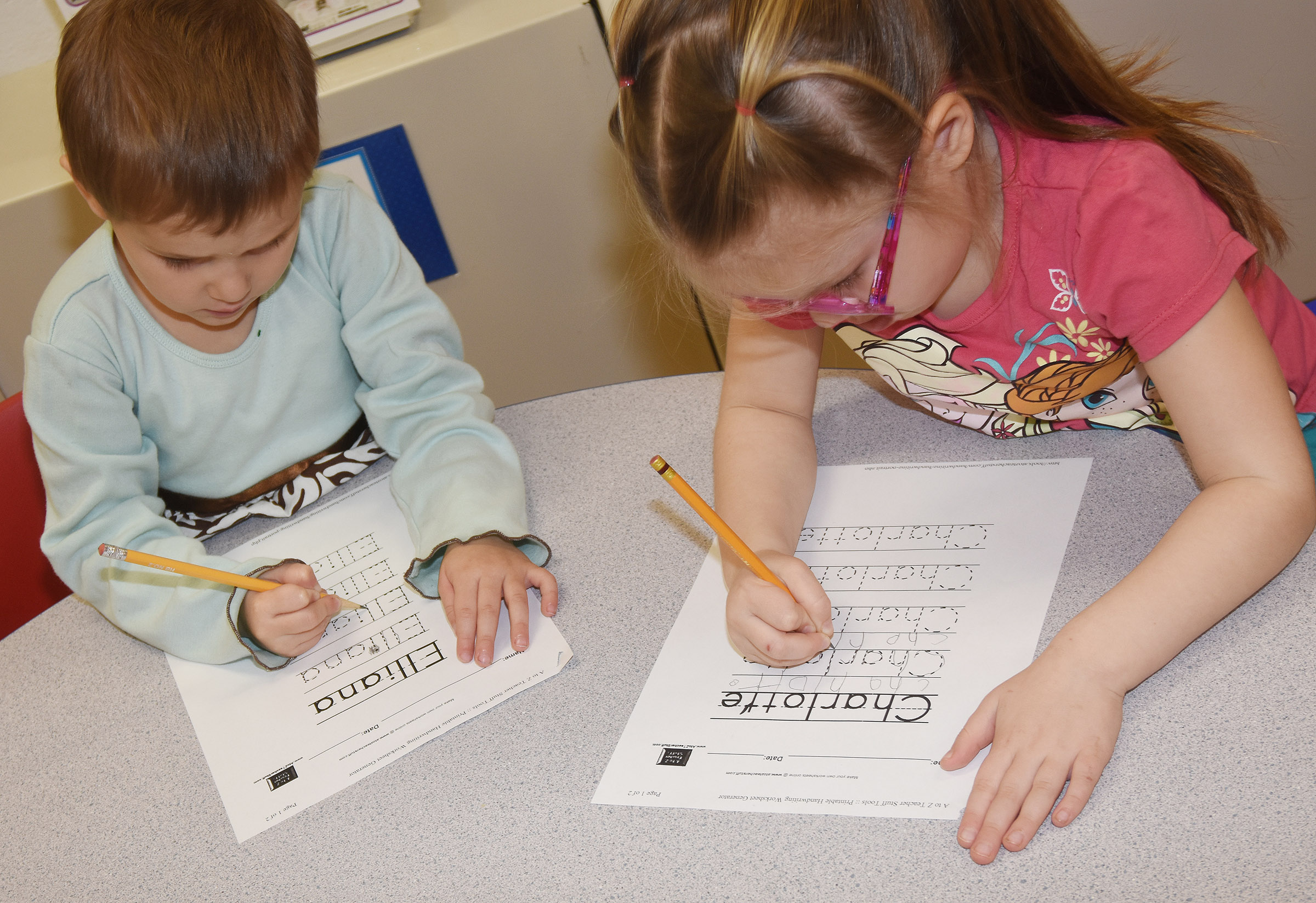 CES preschool students Elliana Morton, at left, and Charlotte Coots practice writing their names.