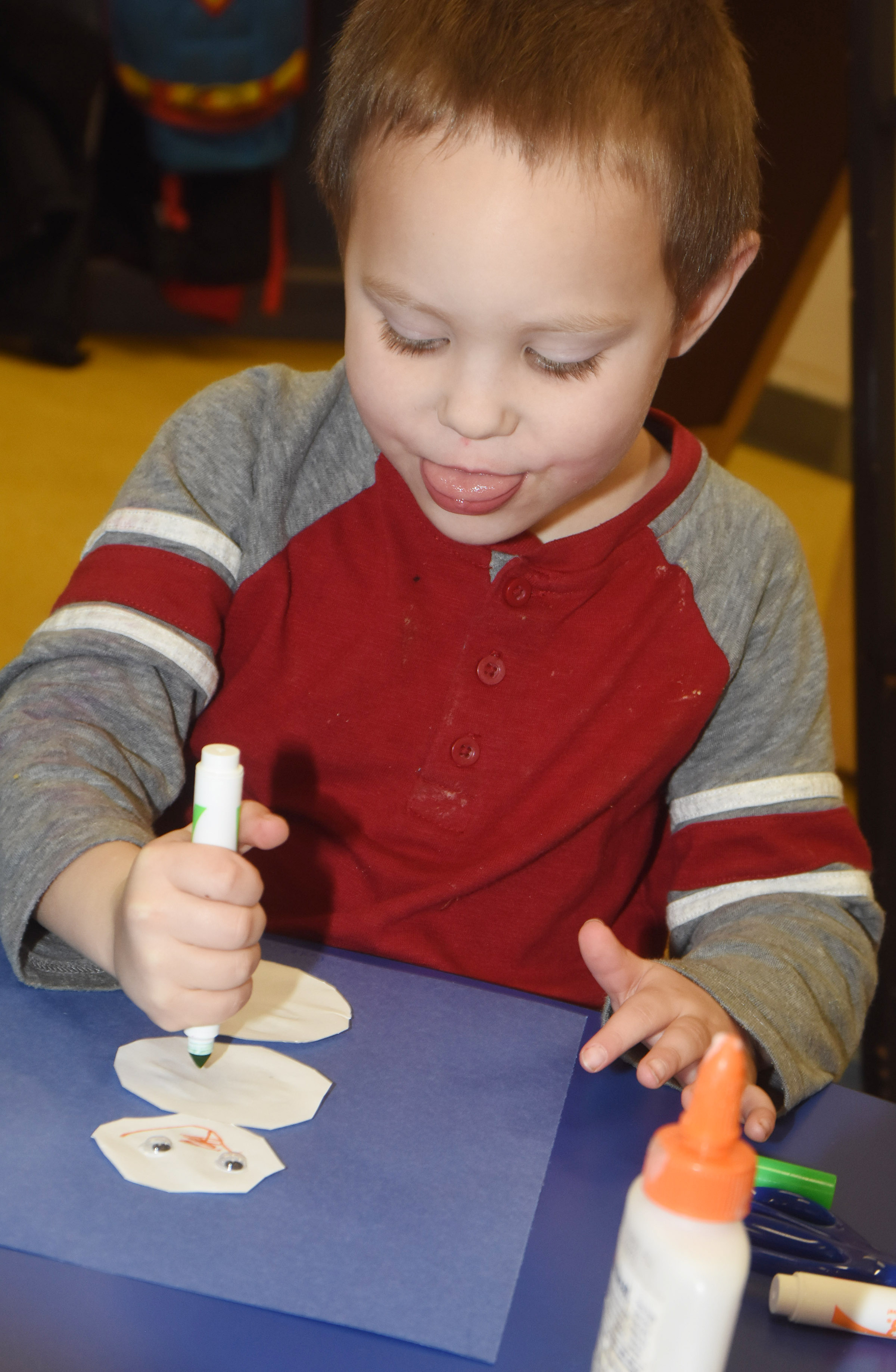 CES preschool student Cole Britton adds a face to his snowman.