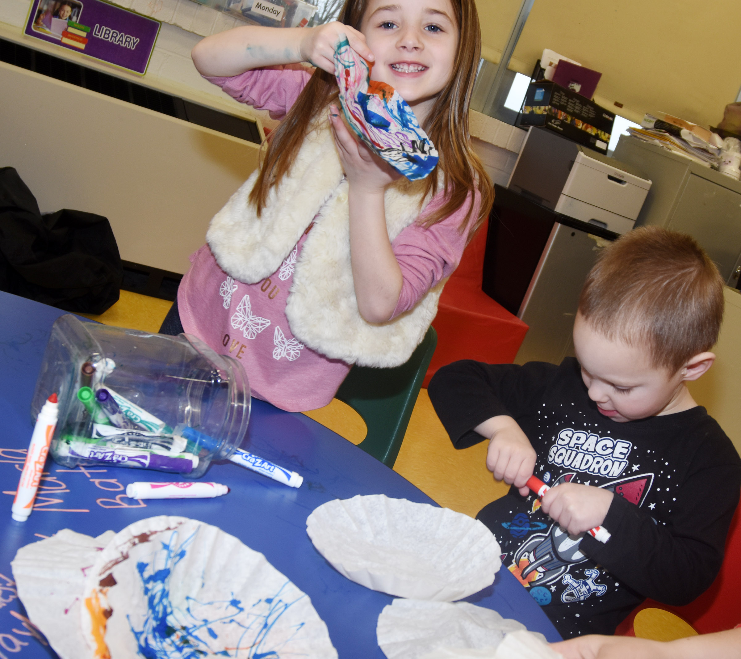 CES preschool student Lylah Davis holds her coffee filter as classmate Cole Britton colors his.