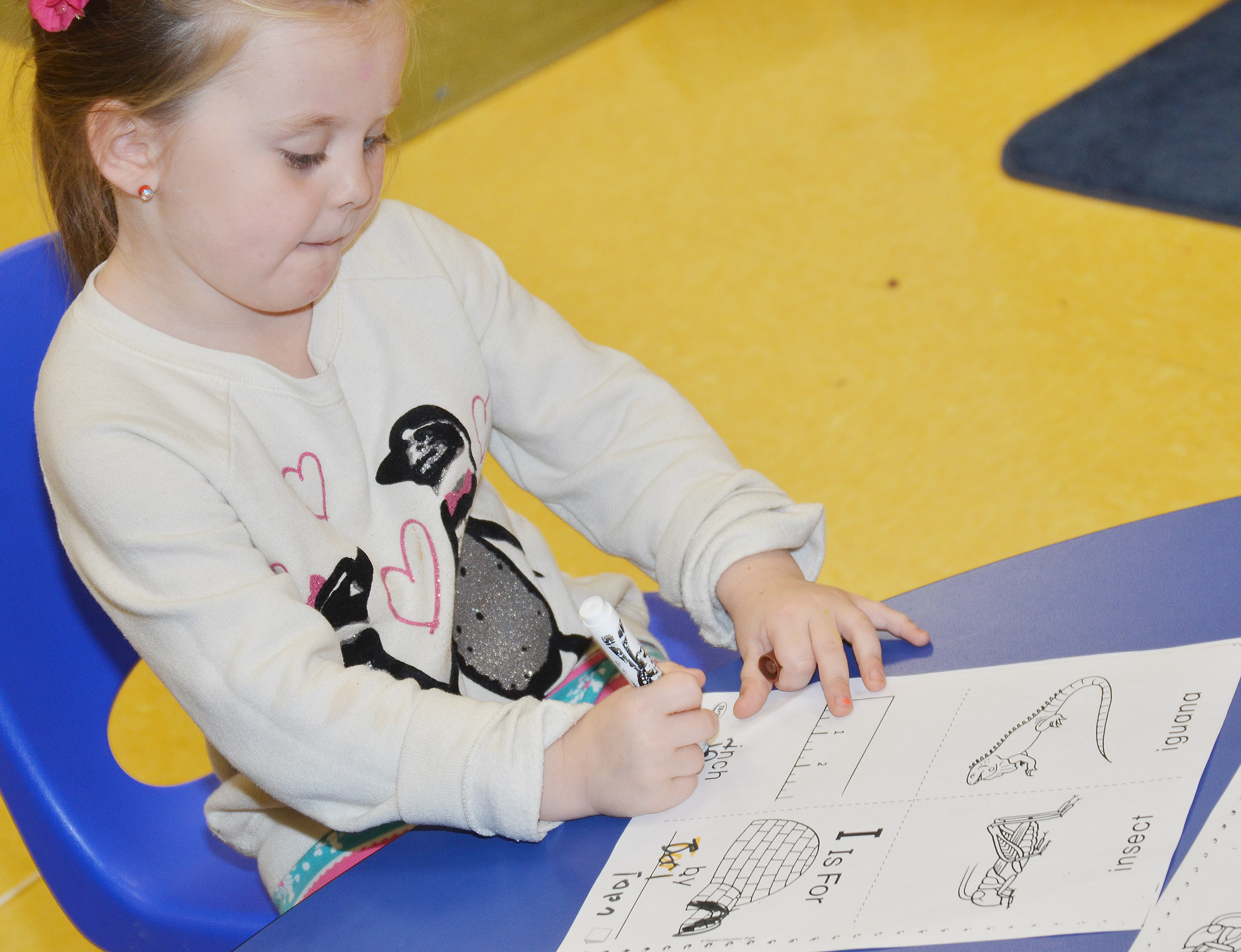 CES preschool student Tori Clark colors her worksheet containing words that start with I.