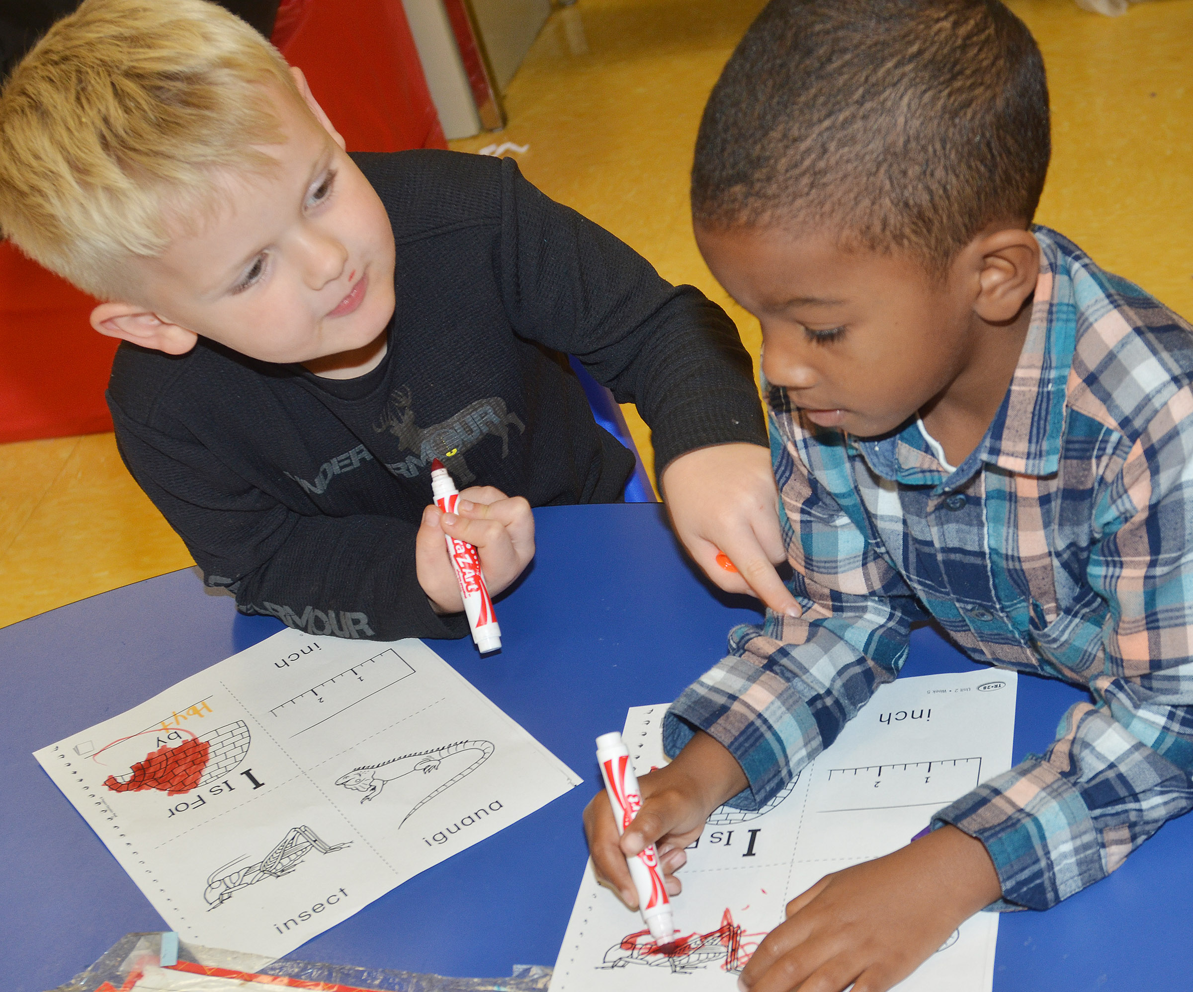 CES preschool students Hoyt Davis, at left, and Rakim Dunn color their worksheets containing words that start with I.