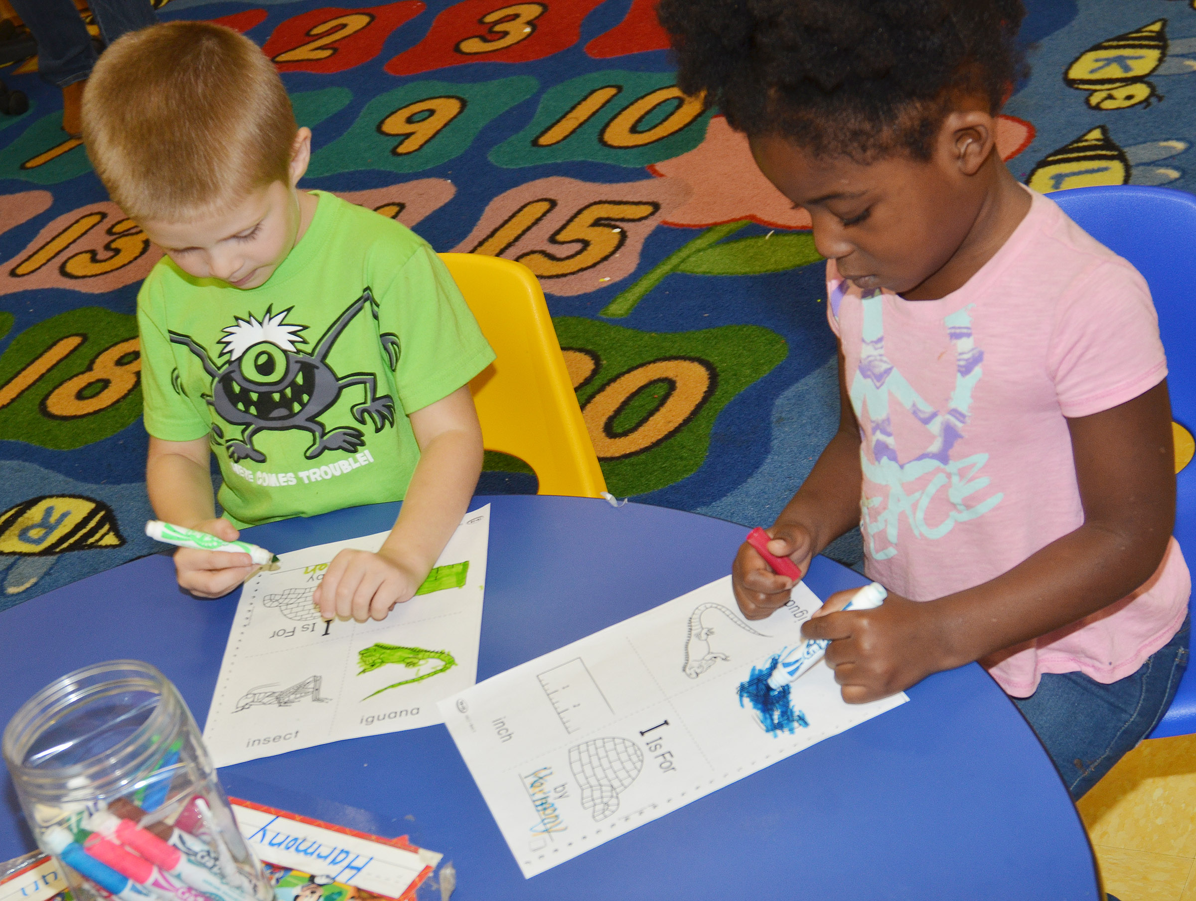 CES preschool students Brian Daniels, at left, and Harmony Brown color their worksheets containing words that start with I.