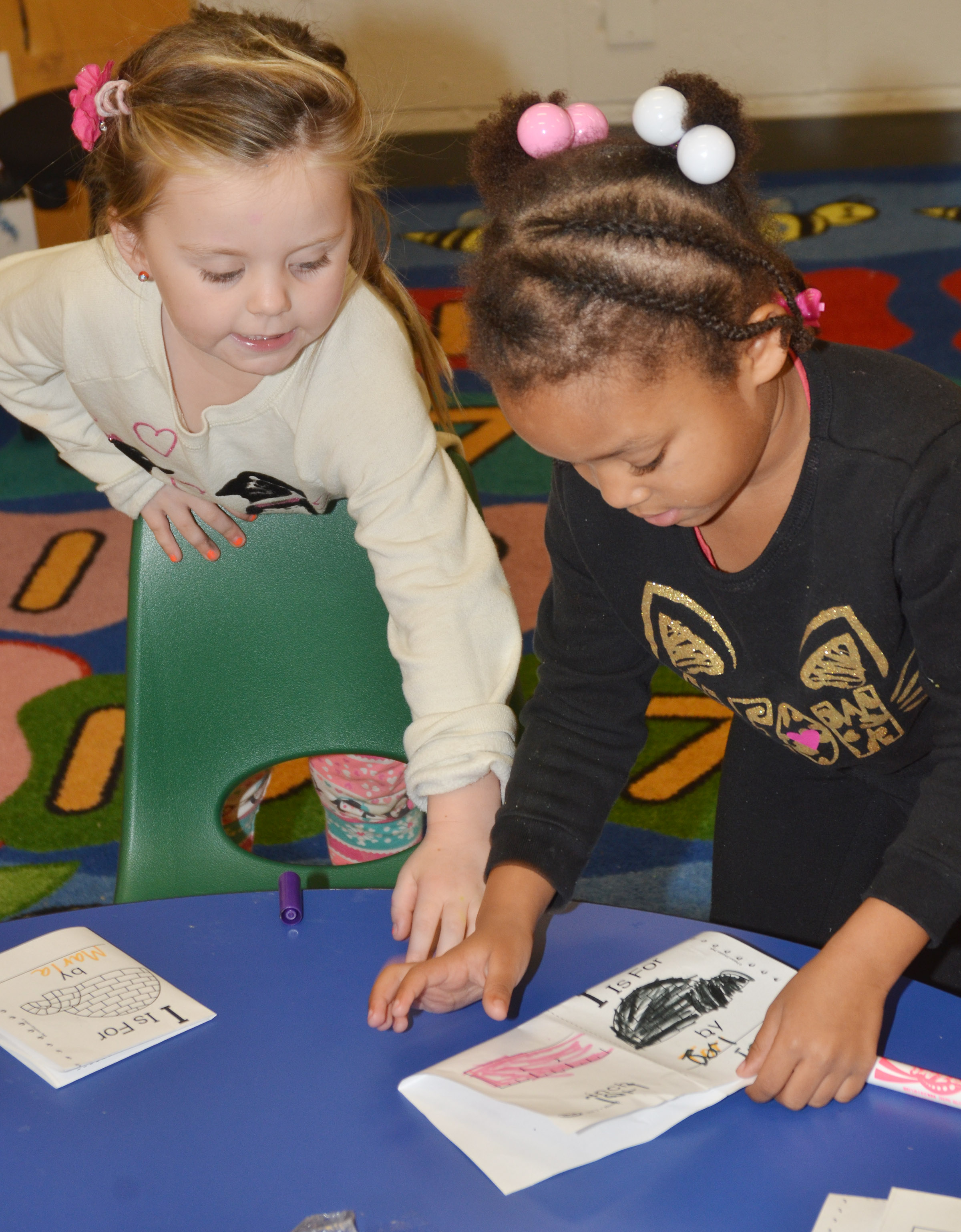 CES preschool students Tori Clark, at left, and Modesty Taylor make books out of their worksheets containing words that start with I.