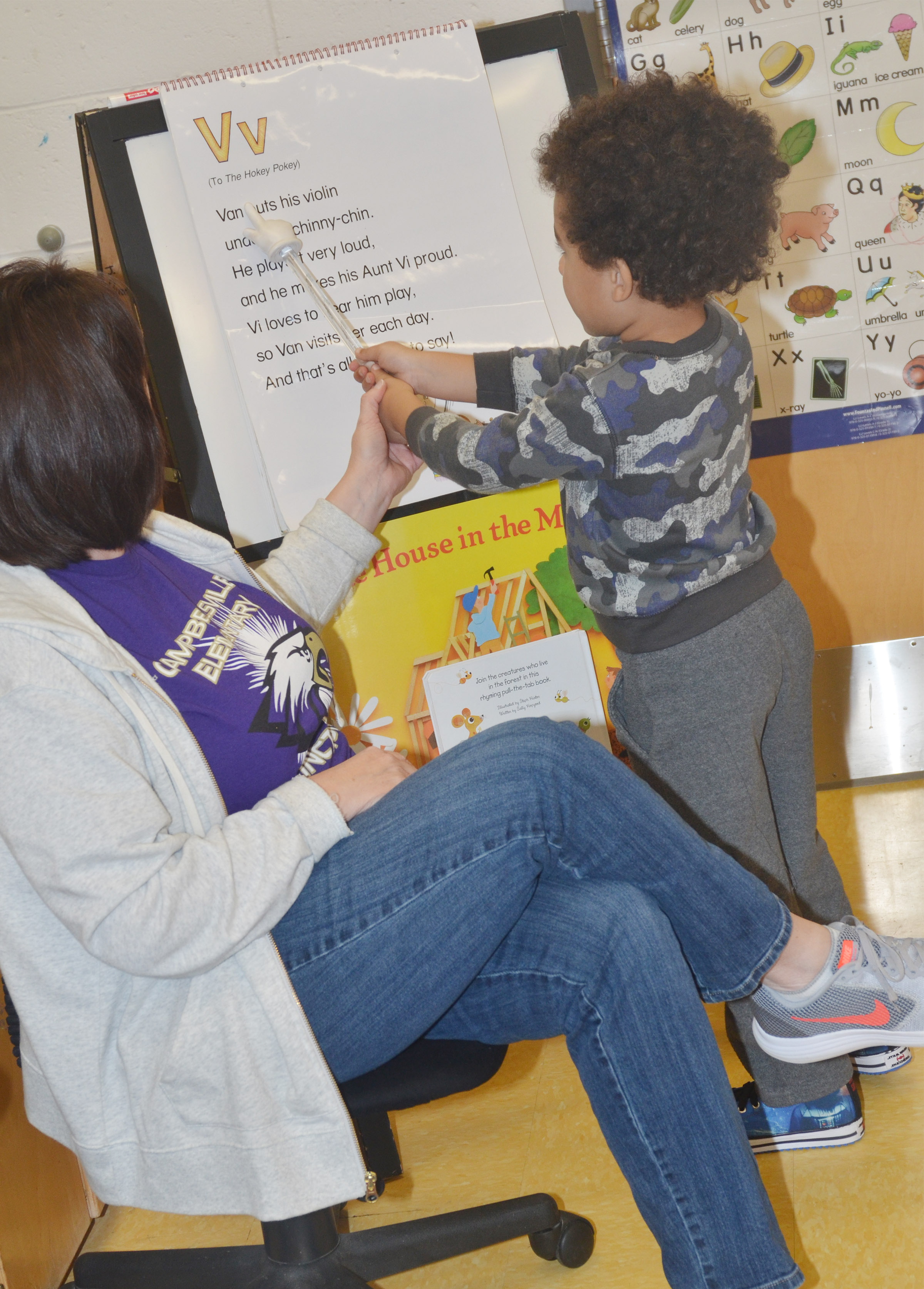 CES preschool teacher Denise Spencer helps Tyrek Moore read a book about the letter V.
