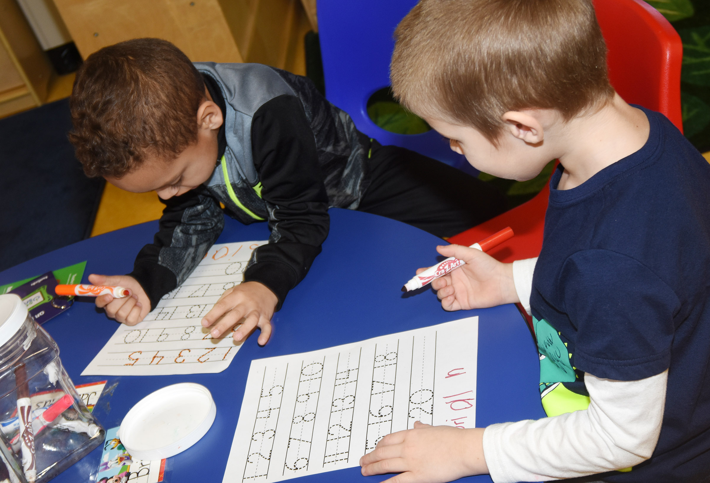 CES preschool students Jasiahas Anderson, at left, and Brian Daniels write the numbers from one to 20.