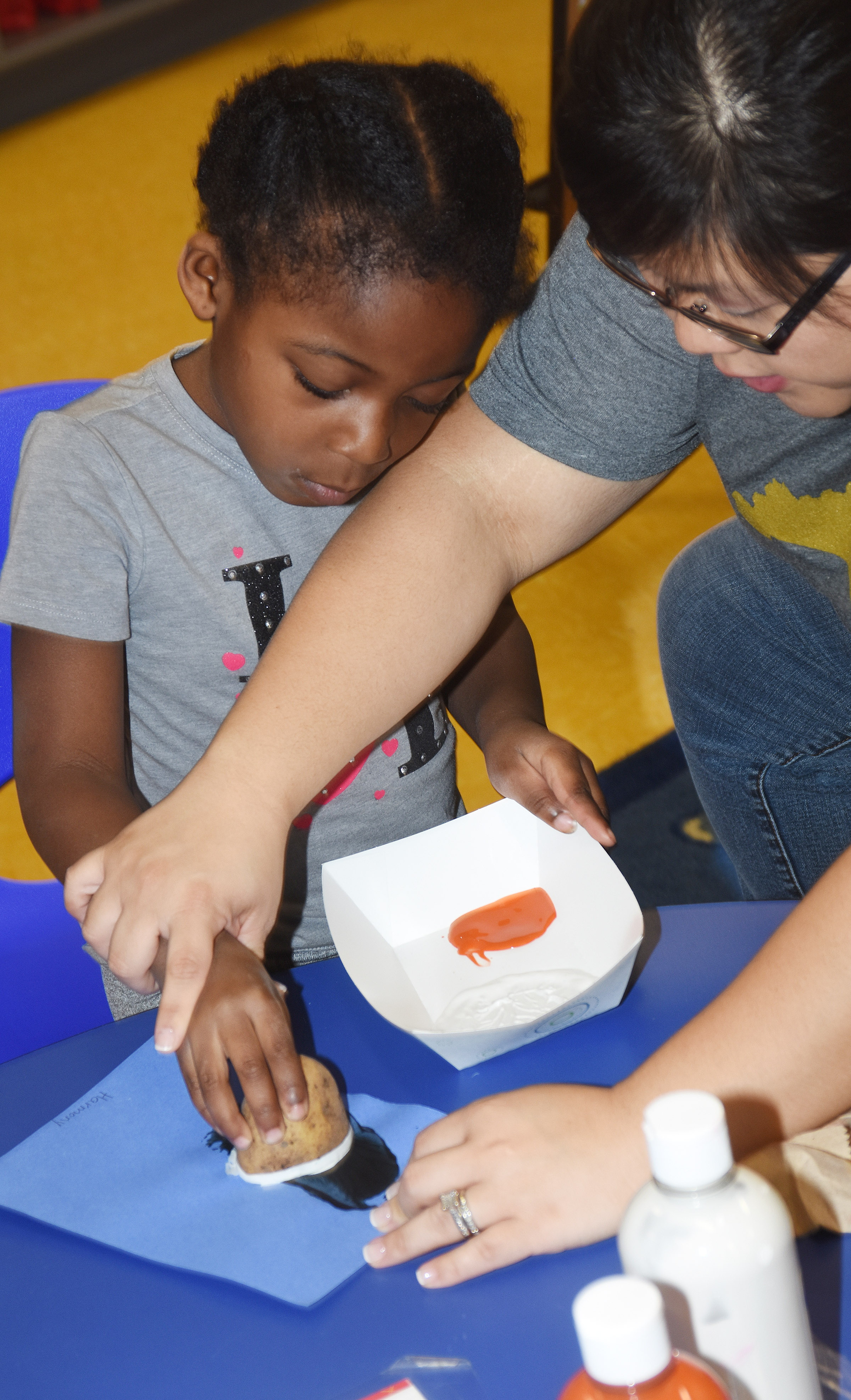 CES Preschool Assistant Brittany Johnson helps Harmony Brown paint her penguin.