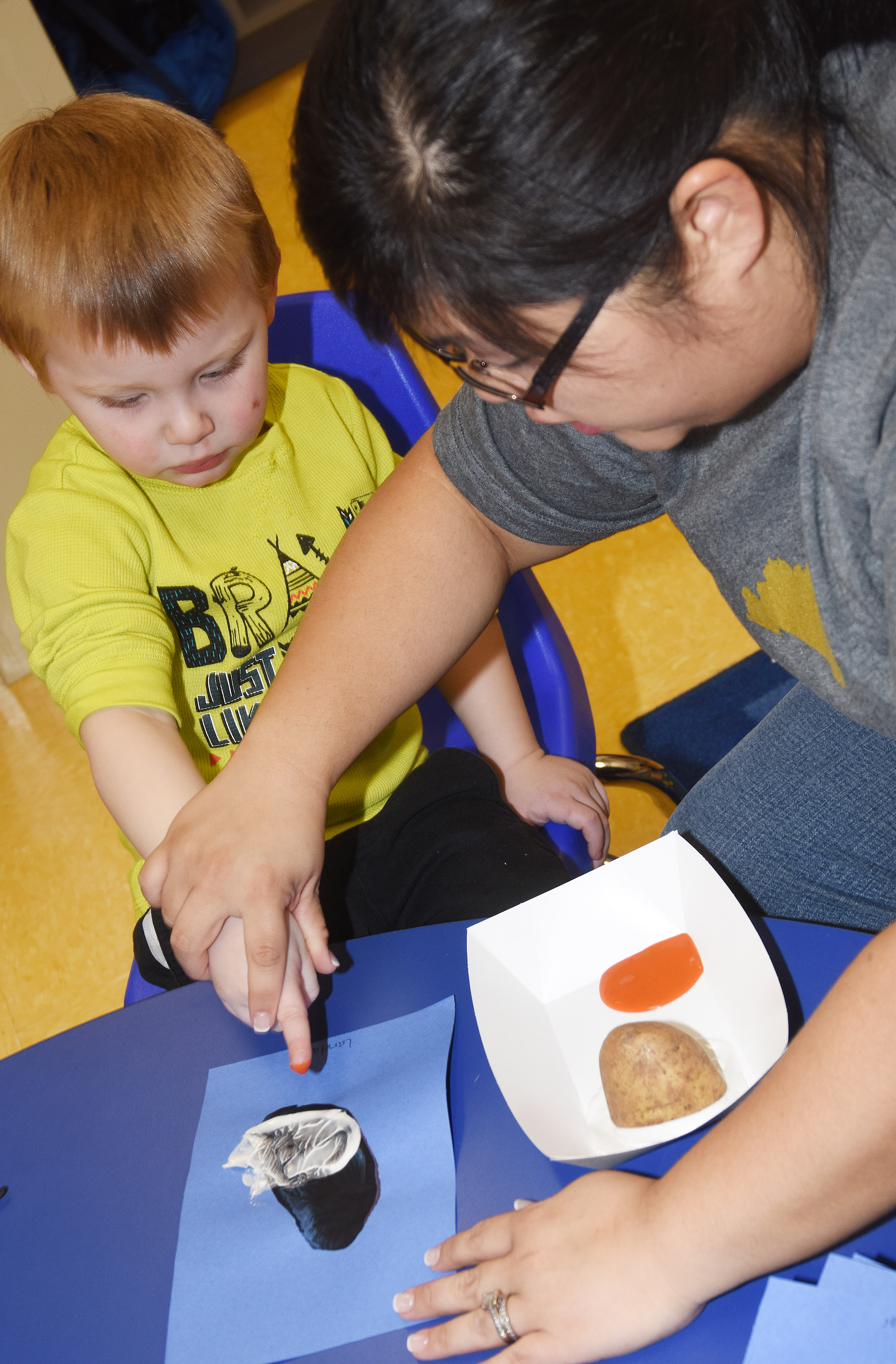 CES Preschool Assistant Brittany Johnson helps Landon Allen add feet to his penguin.