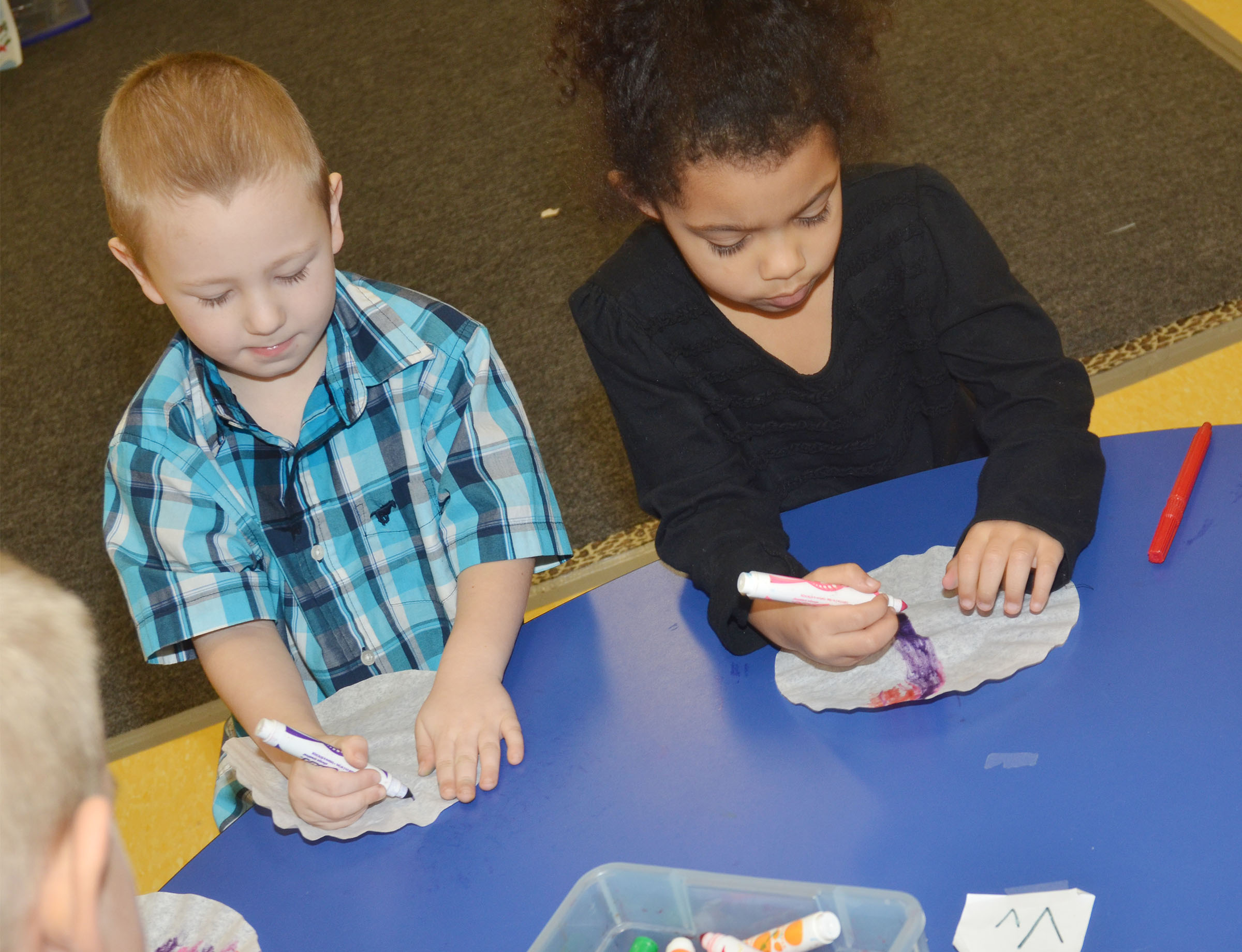 CES preschool students Cameron Dean, at left, and Rylee Karr color their coffee filters.