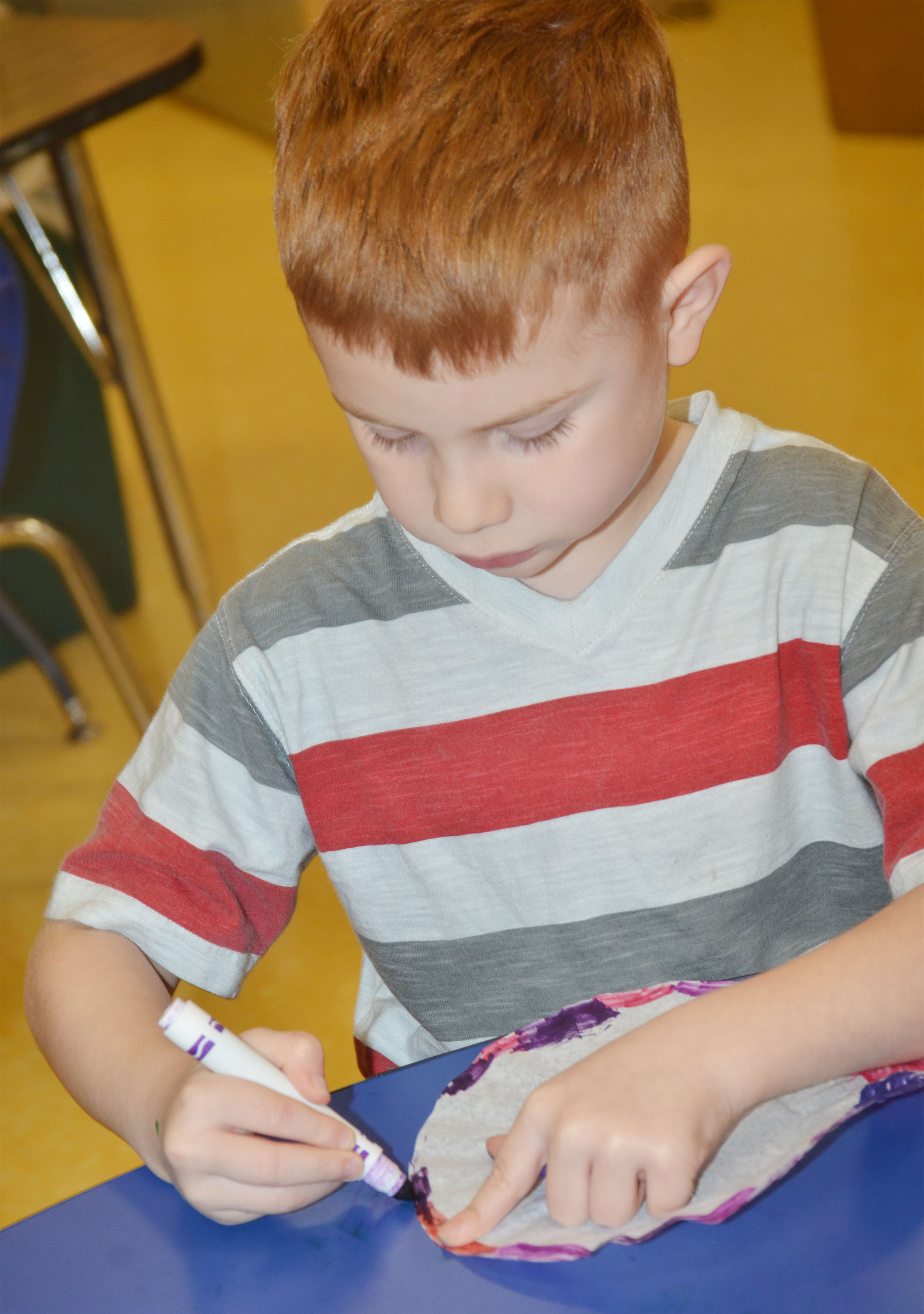 CES preschool student Kennon Dotson colors his coffee filter.