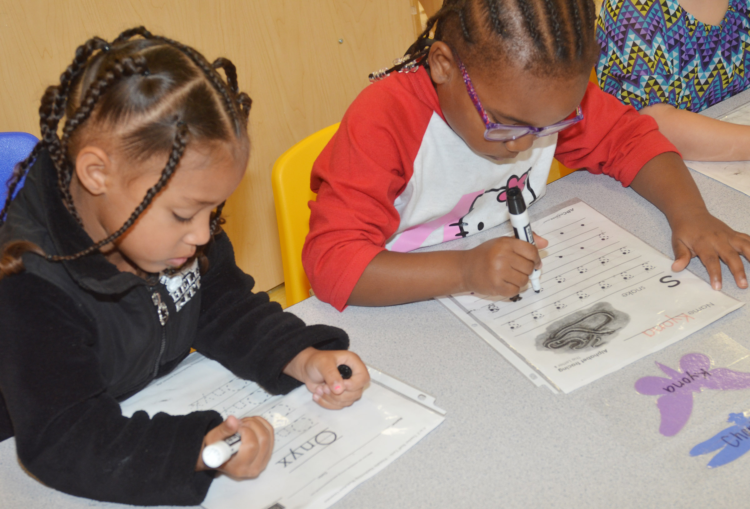 "CES preschool students Onyx Hunter, at left, and Kyona Mitchell practice writing their names and the letter ""s."""