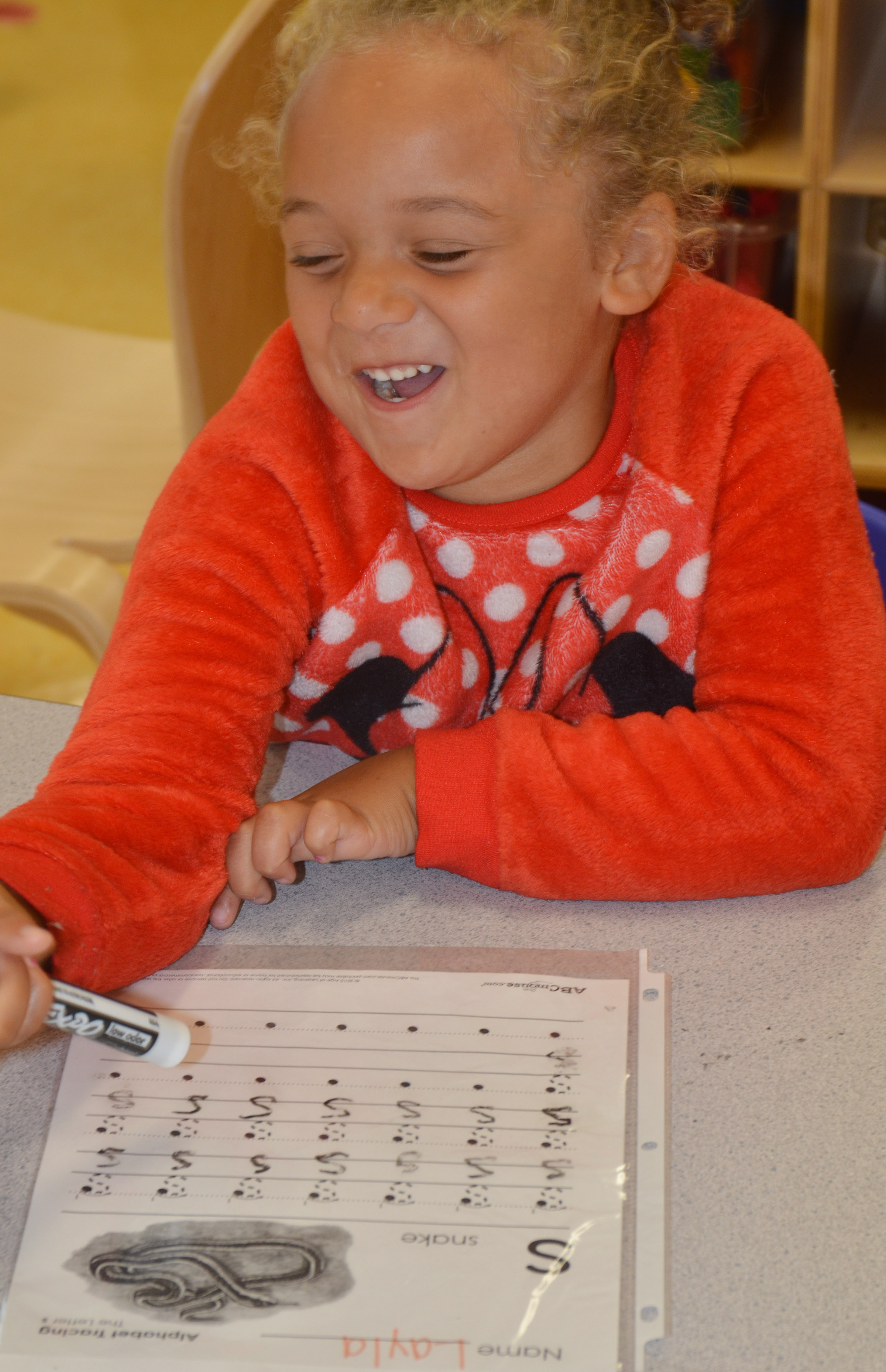 "CES preschool student Layla Barbee laughs as she practices writing the letter ""s."""