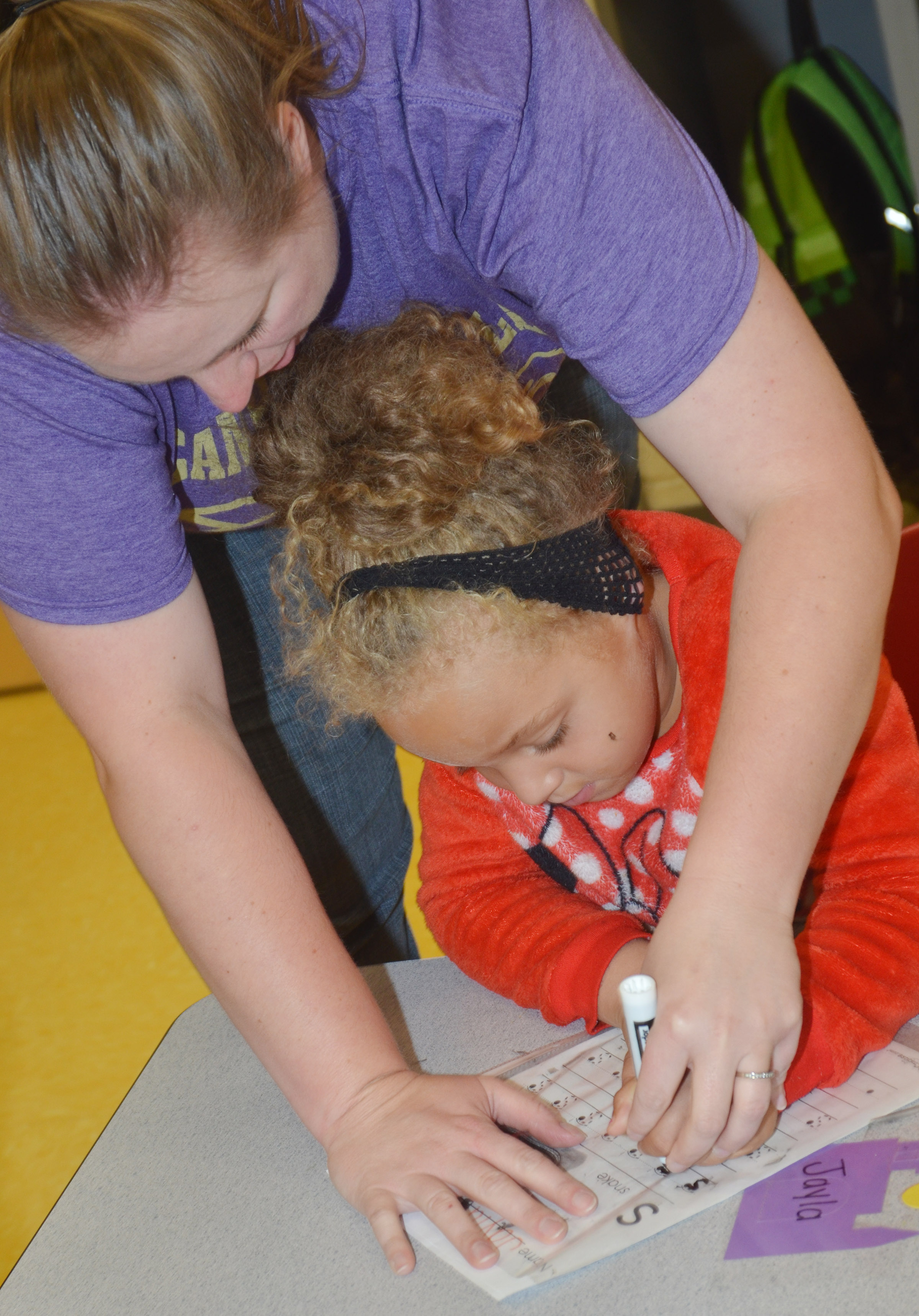 "CES preschool teacher Julie Shelton helps Layla Barbee write the letter ""s."""