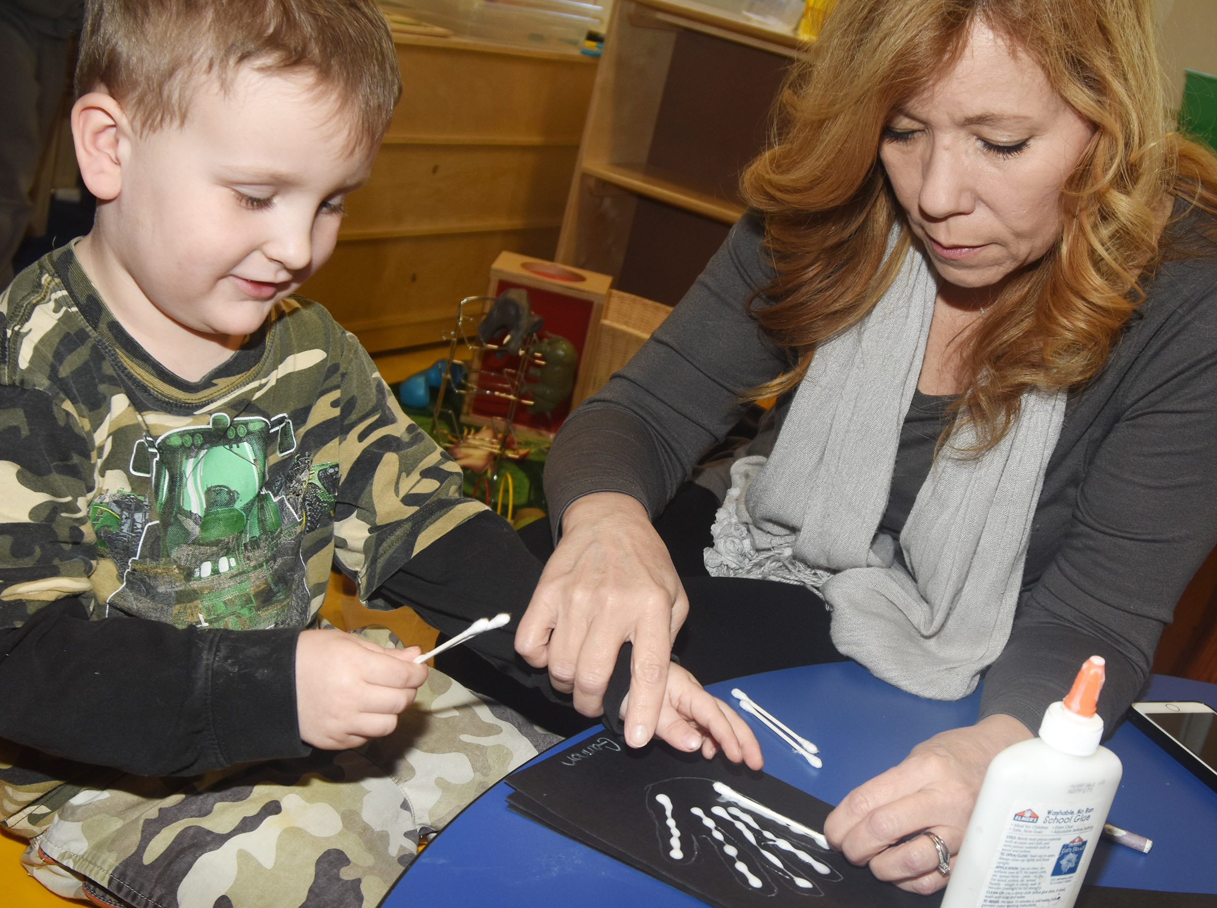 CES preschool substitute Debbie Simmons helps Gannon Scott glue Q-tips on his fingers to make his x-ray.