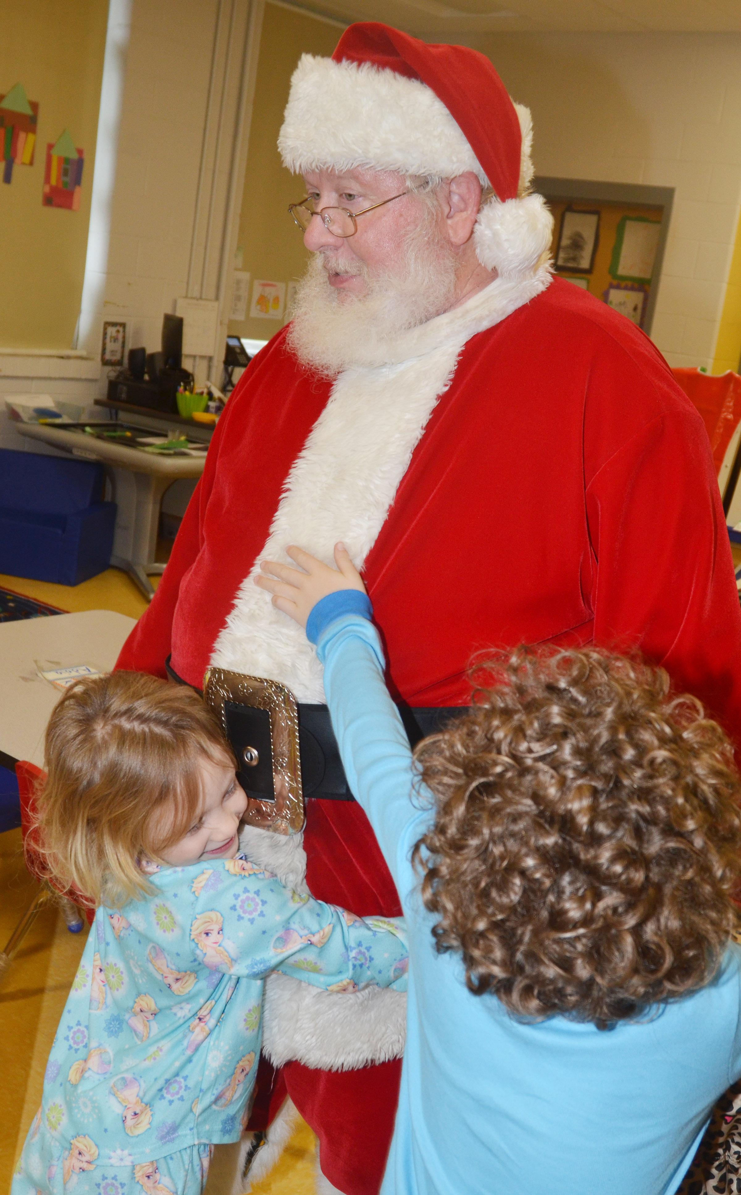 CES preschool students give Santa a hug.
