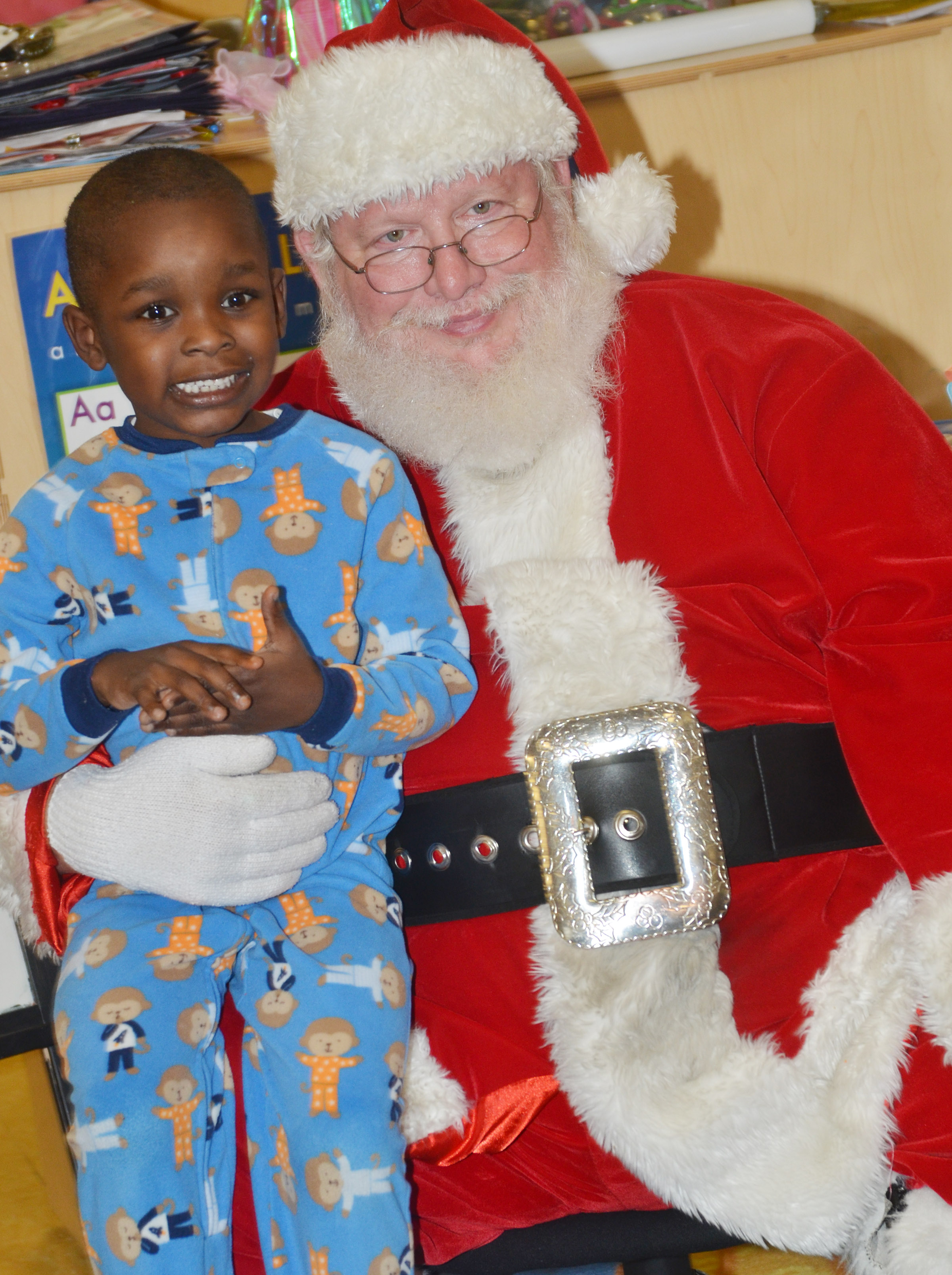 CES preschool student Xavien Smith smiles for a photo with Santa.